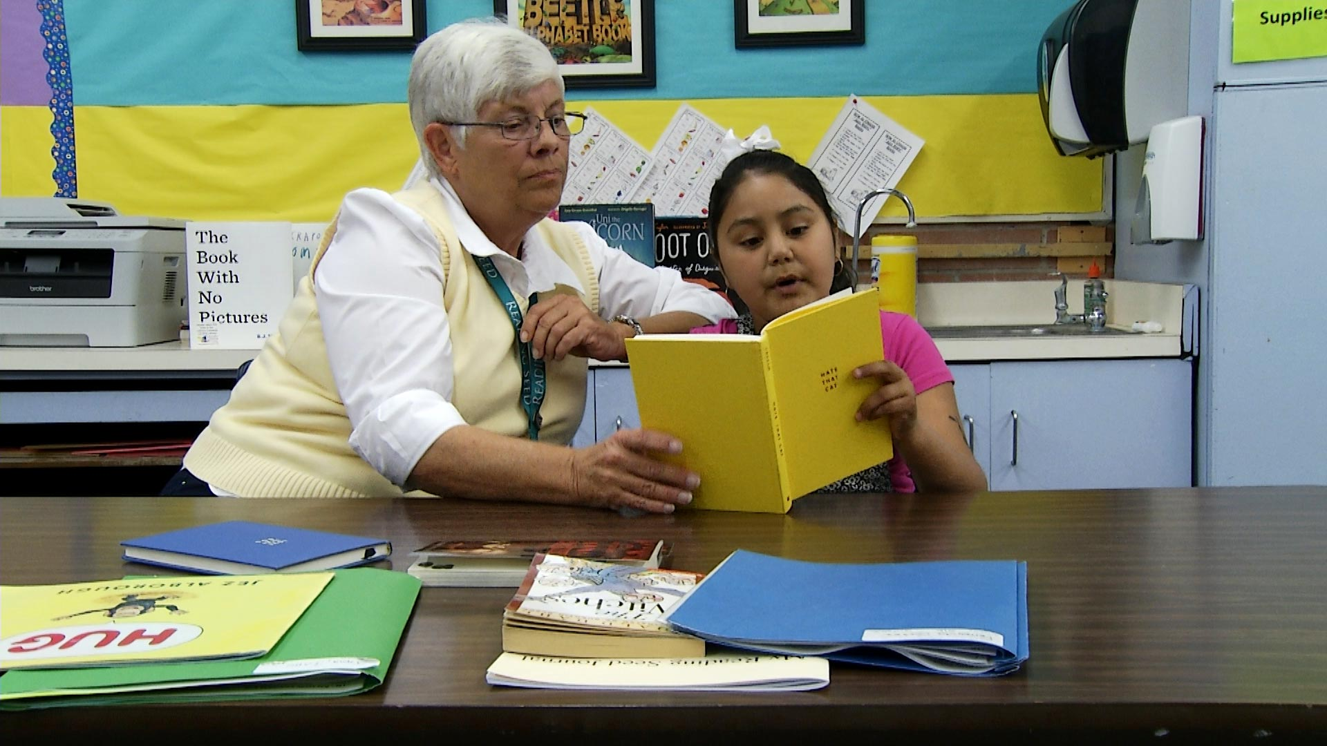 A young girl reads with an educator in class.