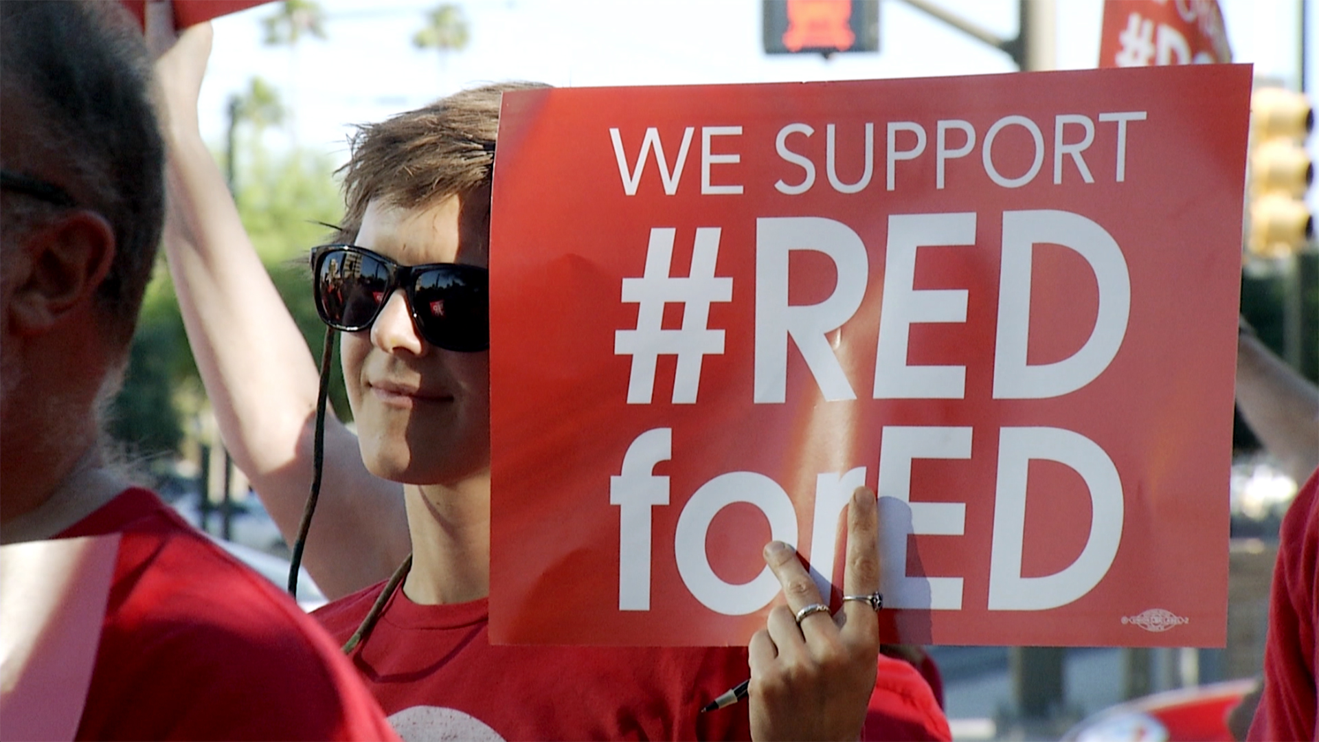 #RedForEd protester stands in the midst of a crowd, April 2019.