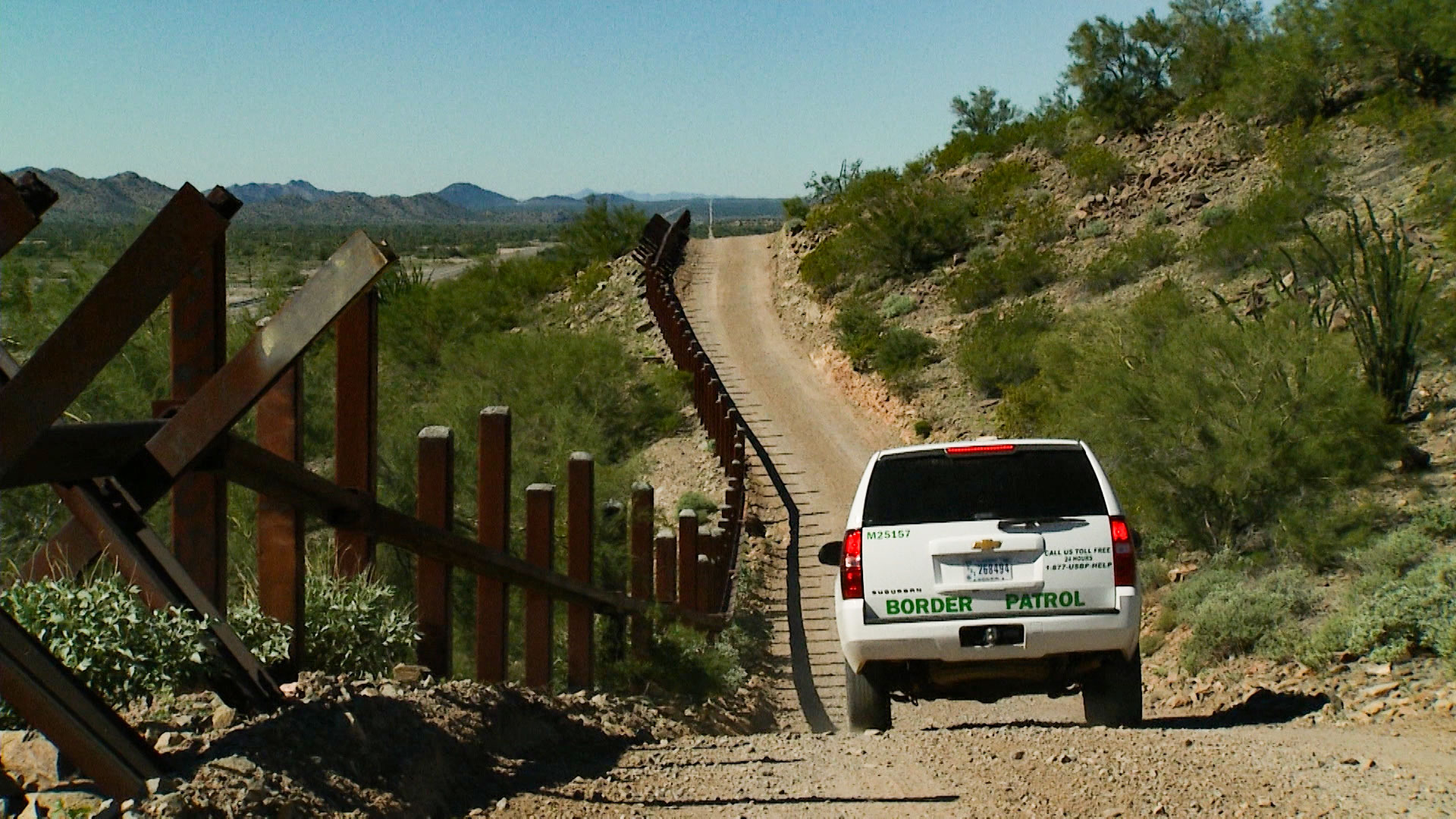 A Border Patrol vehicle drives along a section of fence at the Organ Pipe National Monument, west of Lukeville, Arizona, on Friday, Nov. 2, 2018.