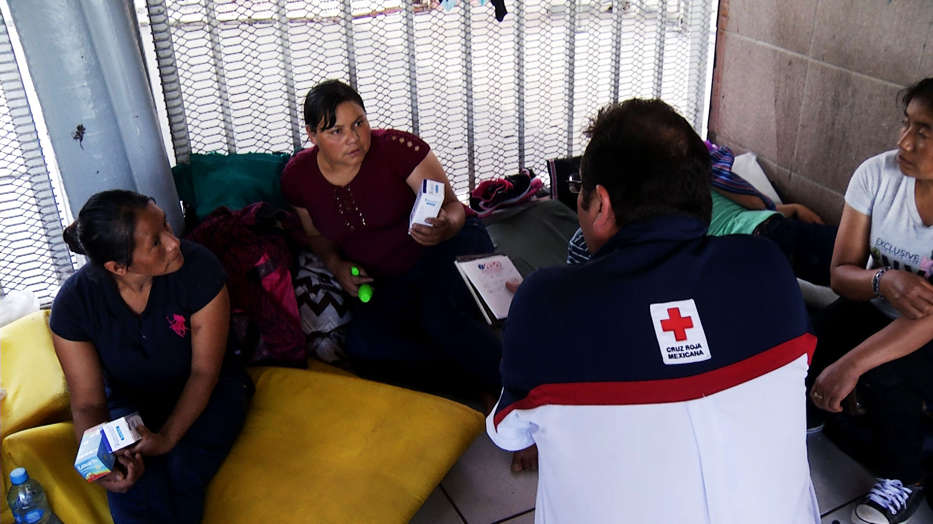A Mexican Red Cross volunteer offers medicine to a woman waiting to make a request for asylum outside the port of entry in Nogales, Sonora on September 4, 2018.