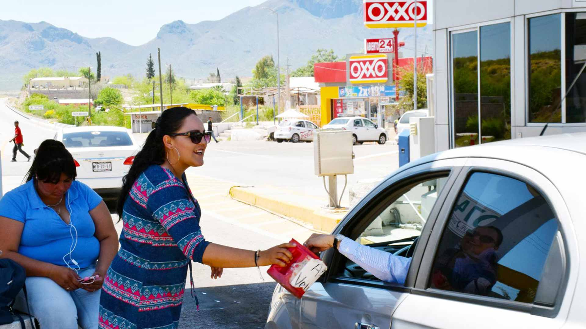 Protester Ana Paula Contreras collects donations from drivers at a toll booth outside Magdalena, Sonora, on the highway that connects Nogales and the capital city of Hermosillo.