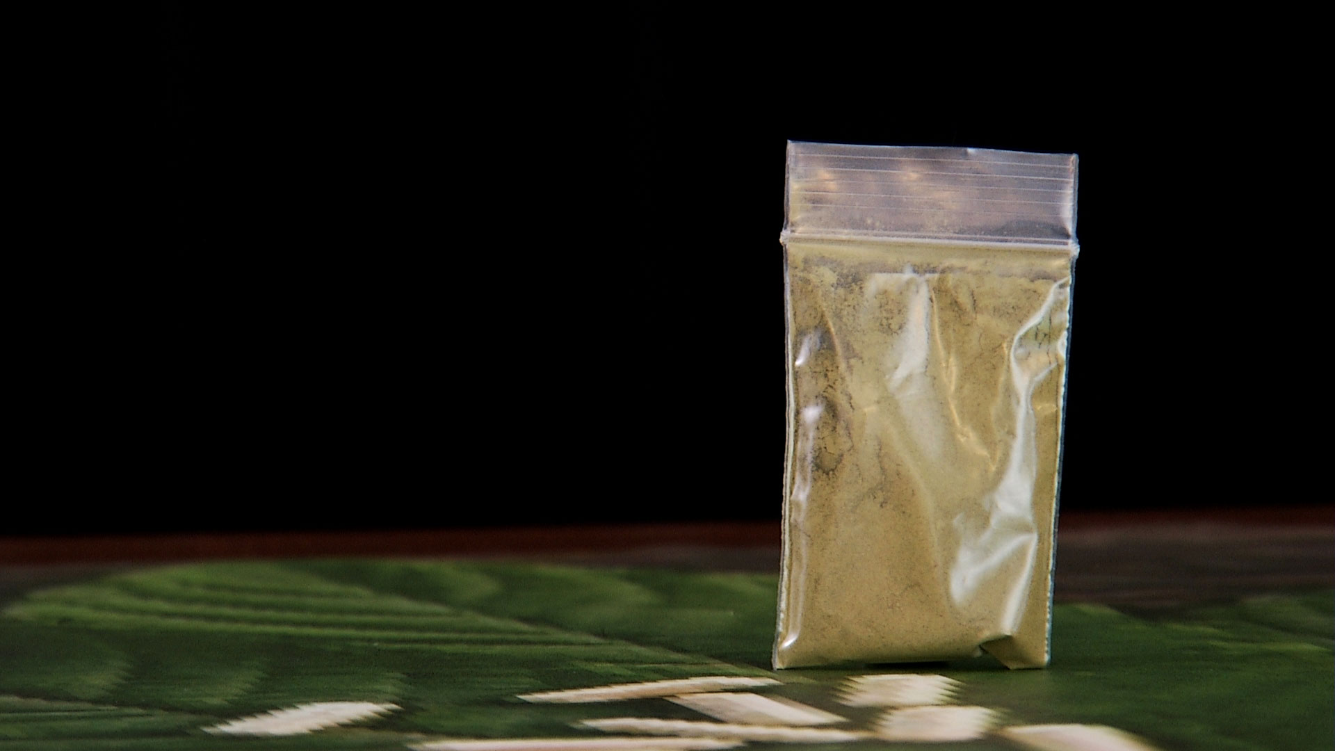 A sealed, plastic bag contains the substance kratom.