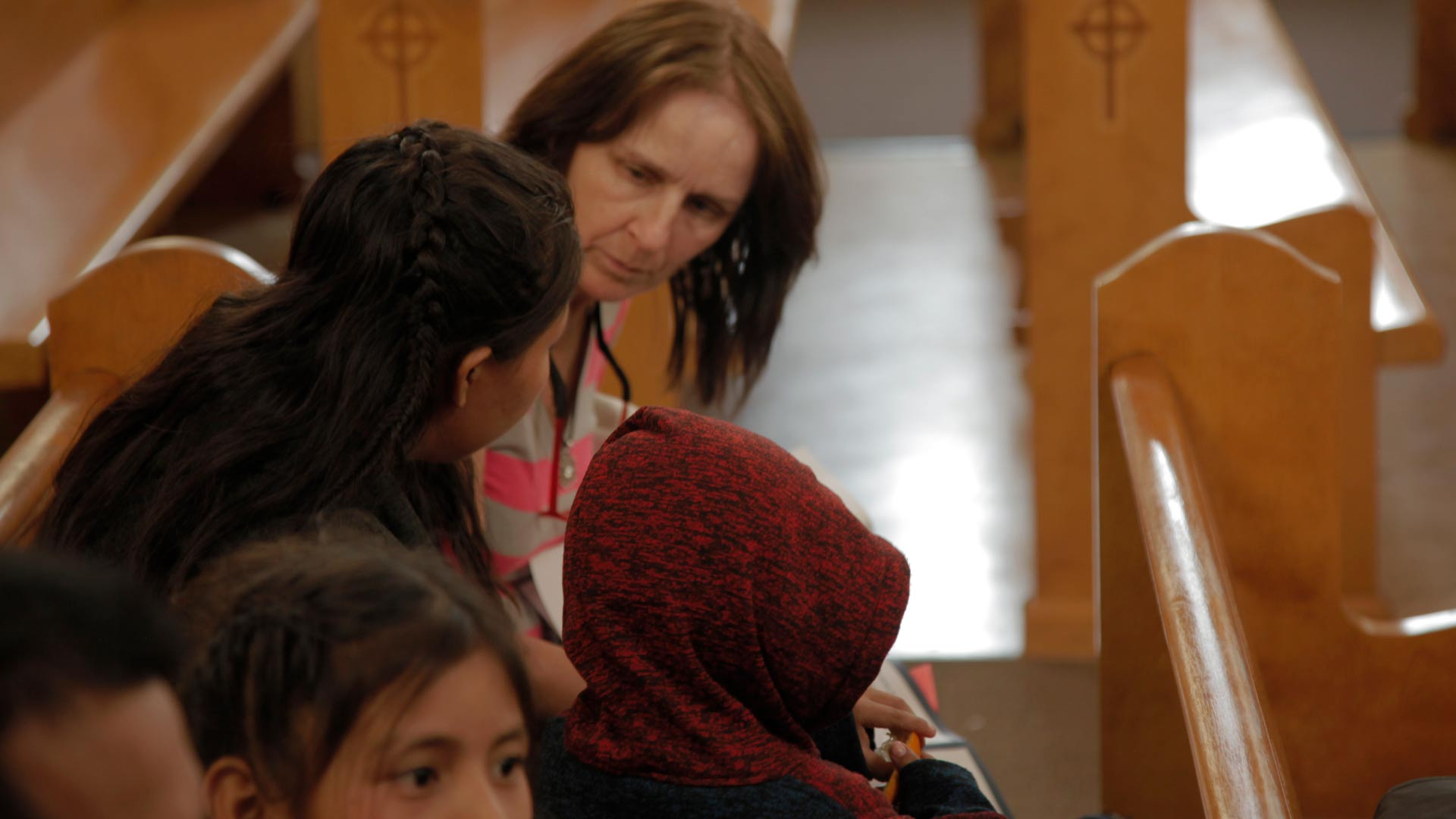 A volunteer at Tucson's Benedictine Monastery reviews when and where an asylum seeking family must appear for an immigration hearing, May 2019.