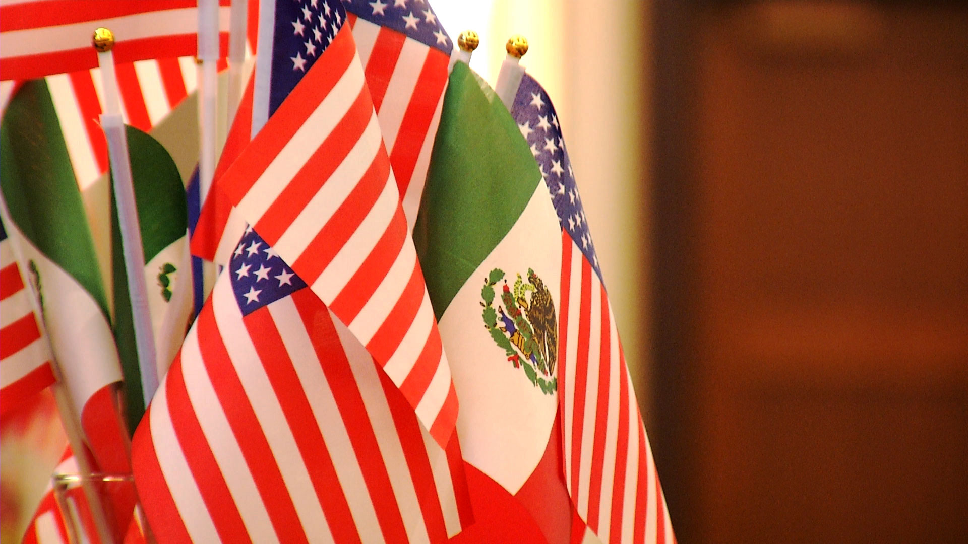 Flags representing the United States and Mexico are bundled together decoratively.
