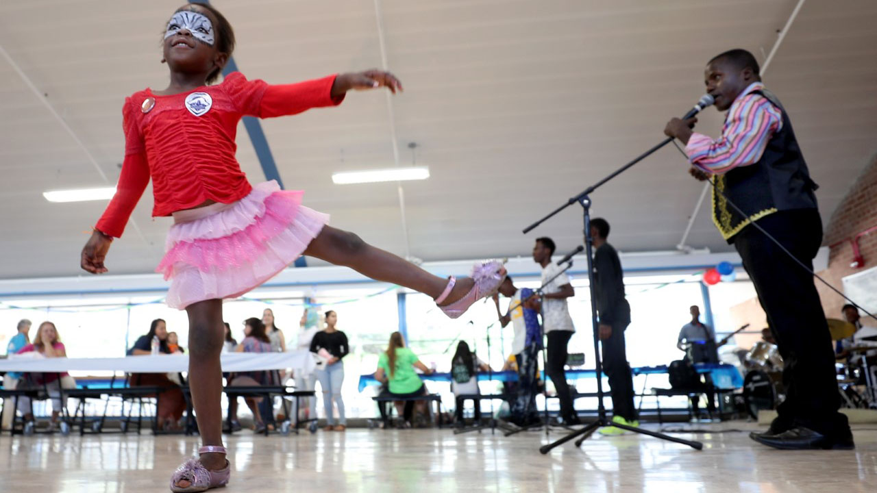 Madeleine Erasto, who's family are refugees from the Congo, dances to the live music at the family fun fest of the World Refugee Day celebration at Catalina High School on Saturday, June 22, 2019, in Tucson.