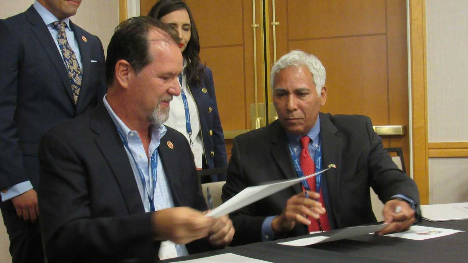 Sonora's Luis Gonzalez (left) hands a signed copy of a memorandum of understanding to Arizona's Matthew Earl Jones on the first day of meetings for the Arizona-Mexico Commission.