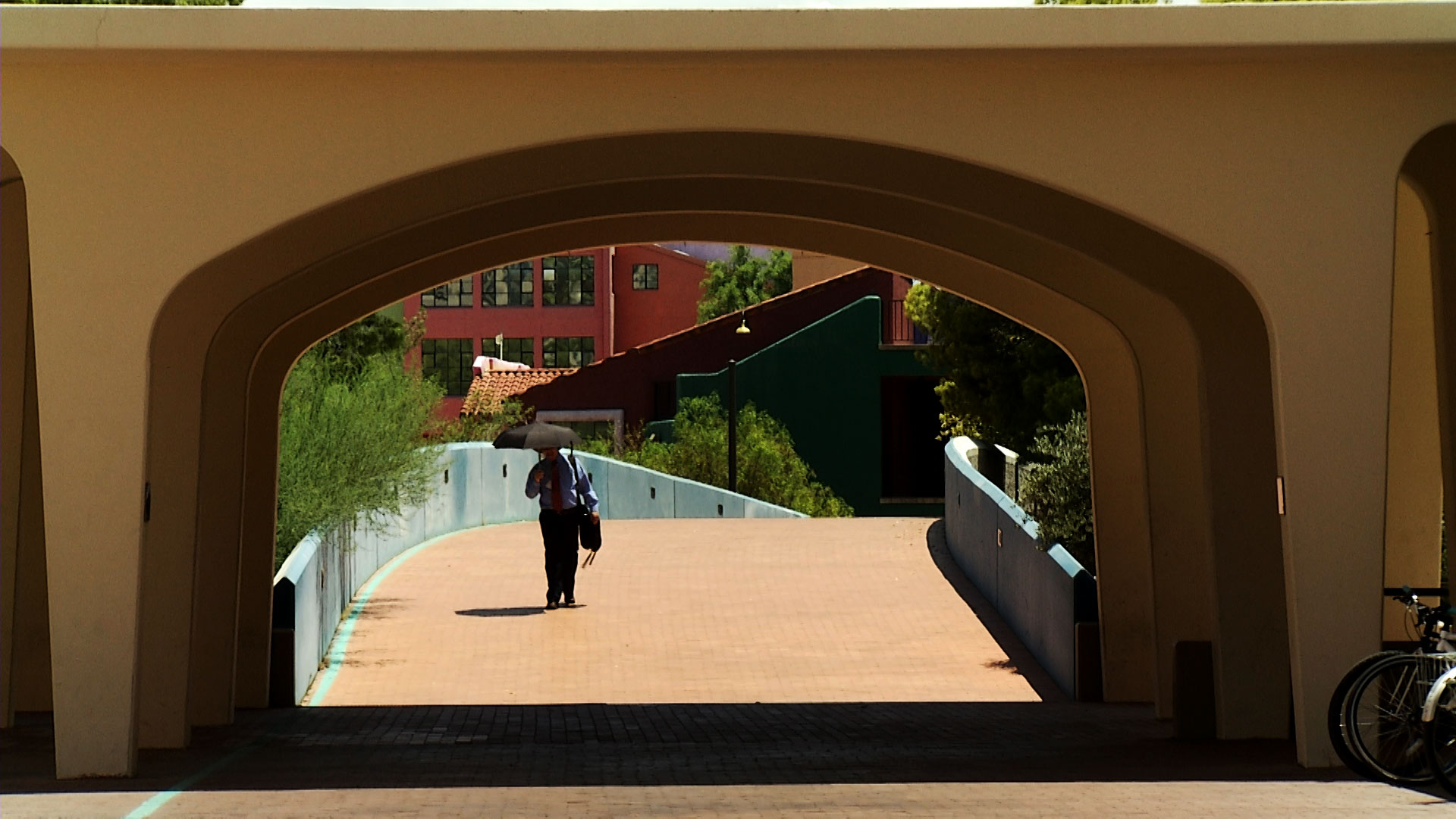 A man walking in downtown Tucson uses an umbrella to shade himself from the sun.