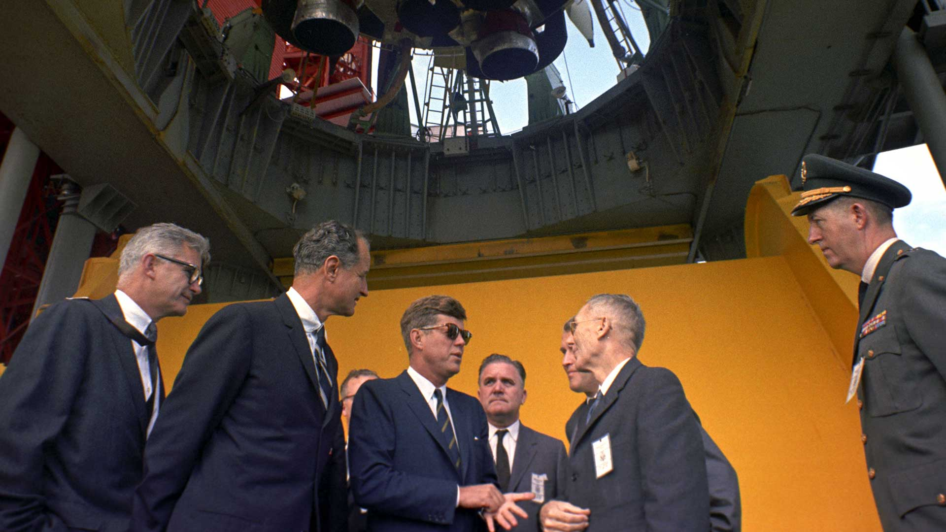 President John F. Kennedy (with sunglasses) is briefed by NASA officials at the Saturn rocket at Pad B, Complex 37, Cape Canaveral, Florida.