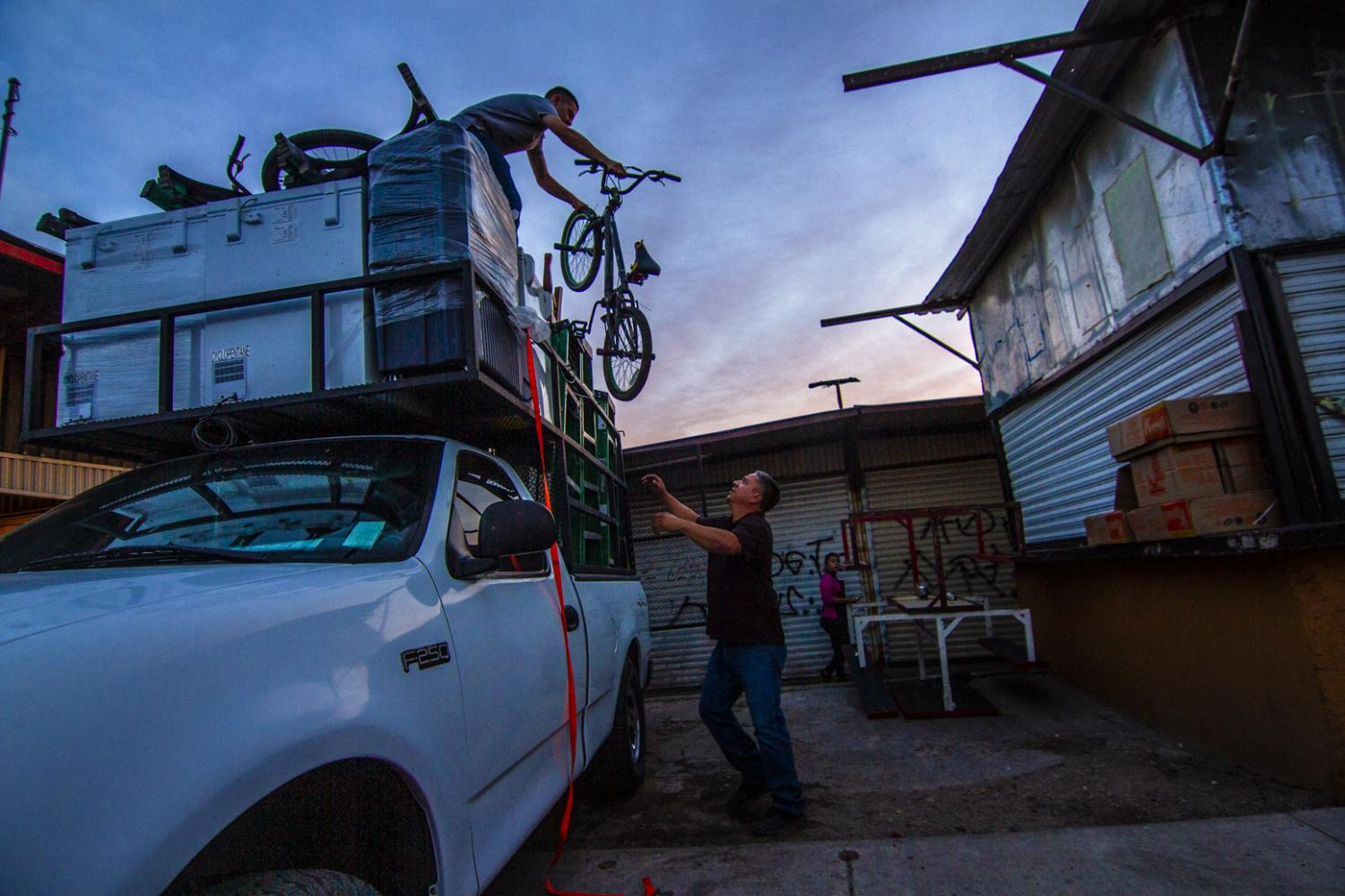 His teenage son, Emilio, hands him a bicycle from the top of a recent load of used Arizona goods that he brought back to the Hector Espino Tianguis.
