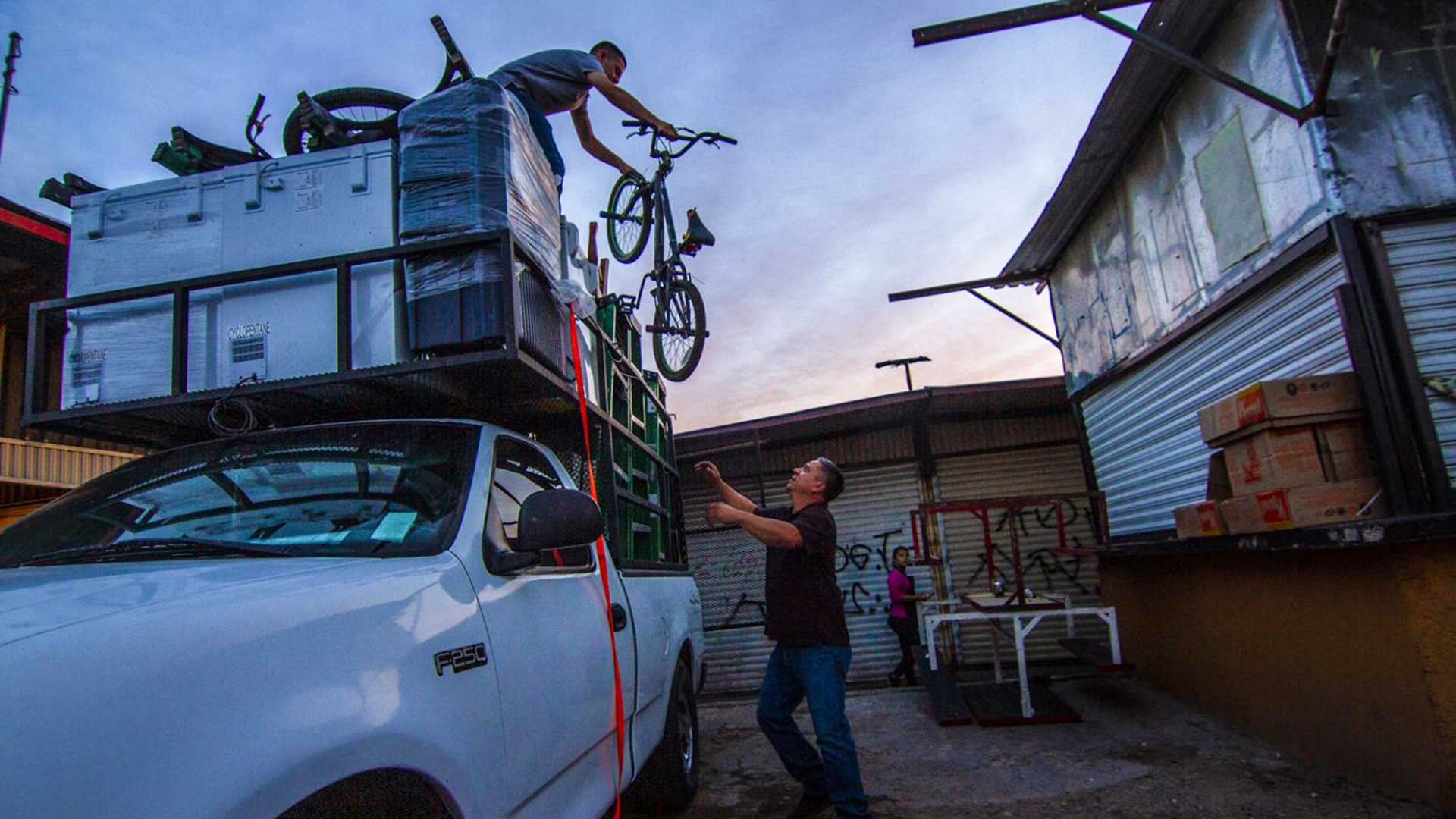 Benito Encinas' teenage son, Emilio, hands him a bicycle from the top of a recent load of used Arizona goods that he brought back to the Hector Espino Tianguis.