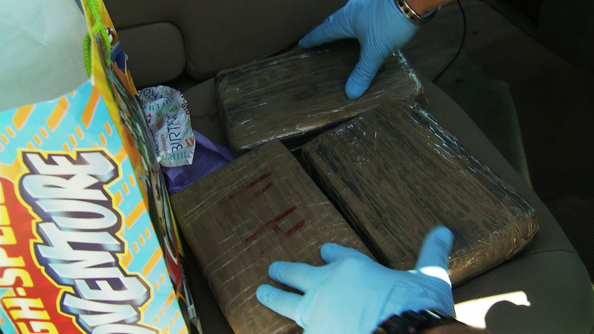 A Pima County Sheriff's deputy removes wrapped bundles of cocaine discovered hidden in a gift bag during a traffic stop in June 2019.
