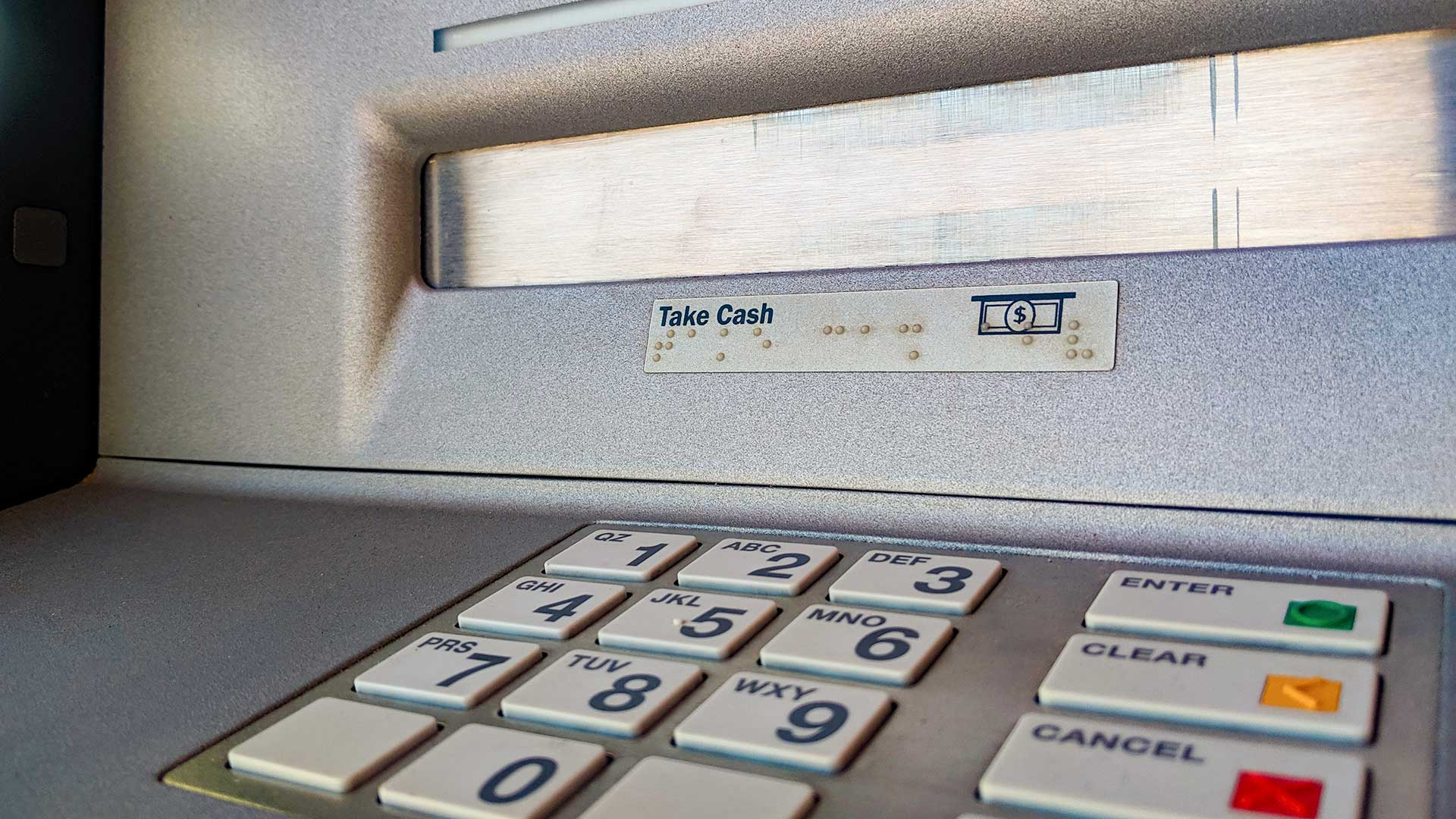 The number pad and cash dispenser at an ATM.
