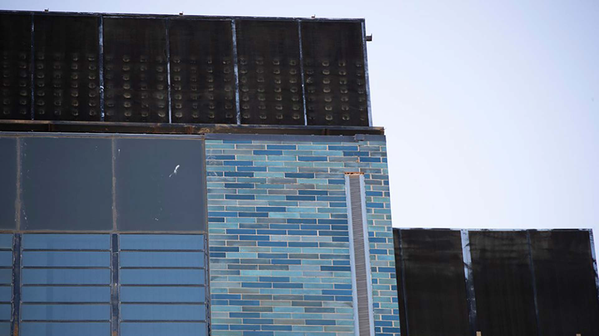 This image distributed by Pima County via social media on Aug. 14, 2019 shows a part of the county's Legal Services Building, where distinctive blue-green bricks have dislodged. Efforts are underway to find and repair loose bricks on the the building, built in 1967.