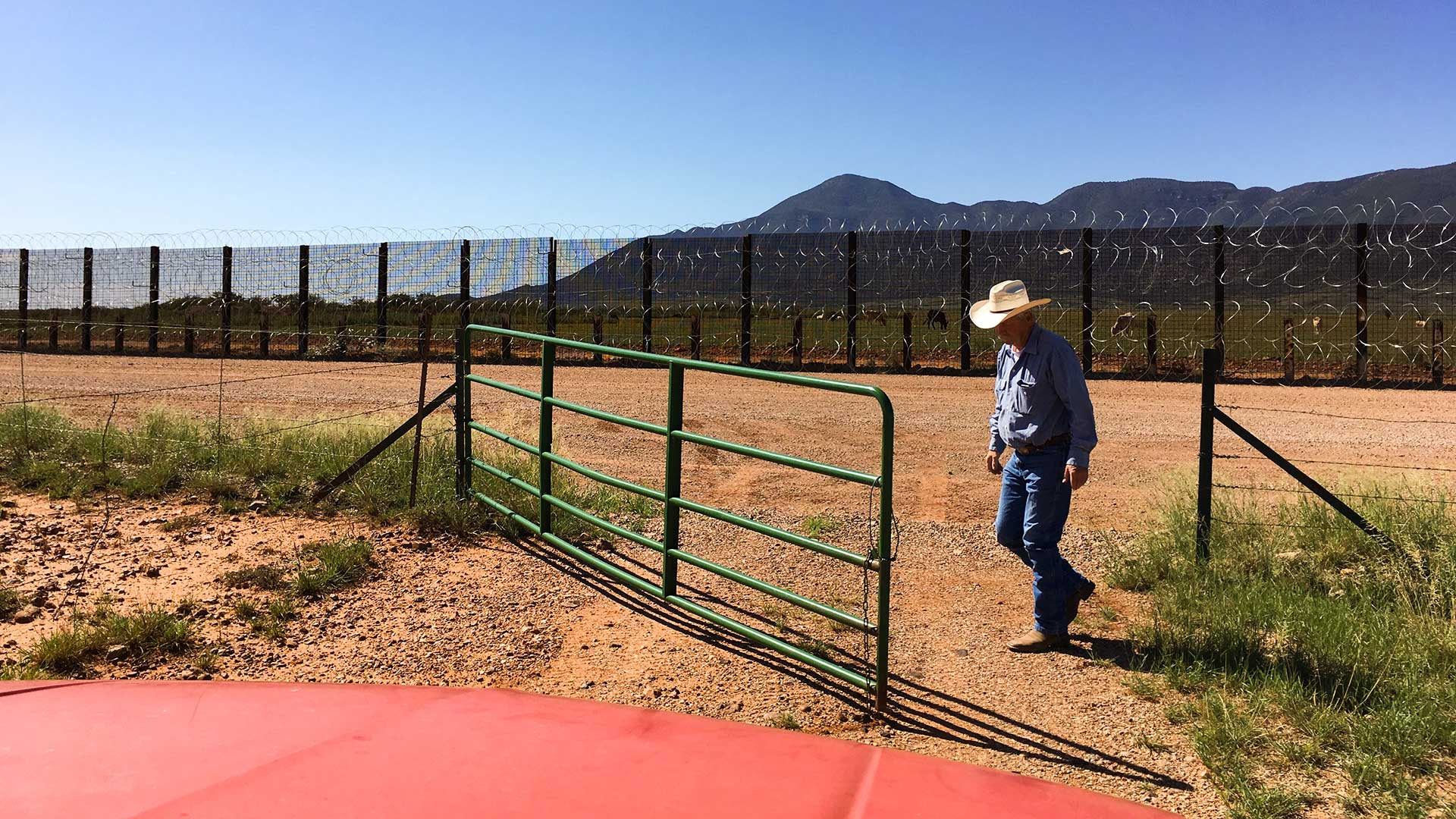 Rancher John Ladd opens a gate on his property where it meets the U.S.-Mexico border fence.