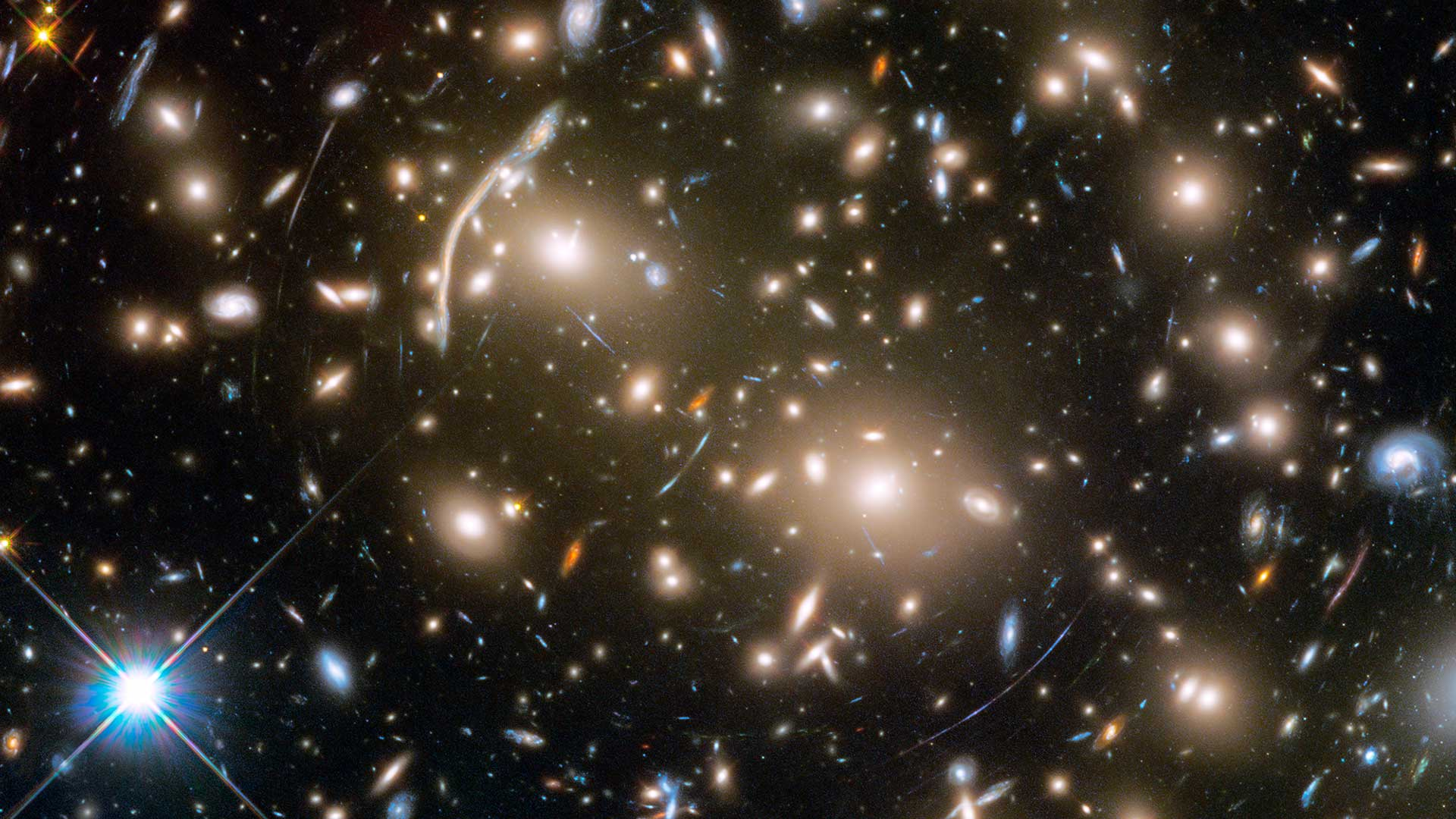 The Hubble Space Telescope took this image of Abell 370, a galaxy cluster 4 billion light-years from Earth. Several hundred galaxies are tied together by gravity. The arcs of blue light are distorted images of galaxies far behind the cluster.