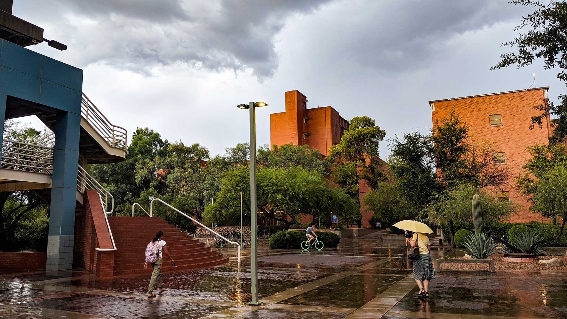 People on the University of Arizona campus take advantage of a lull in a summer rain storm to get to where they're going, Aug. 28, 2019.