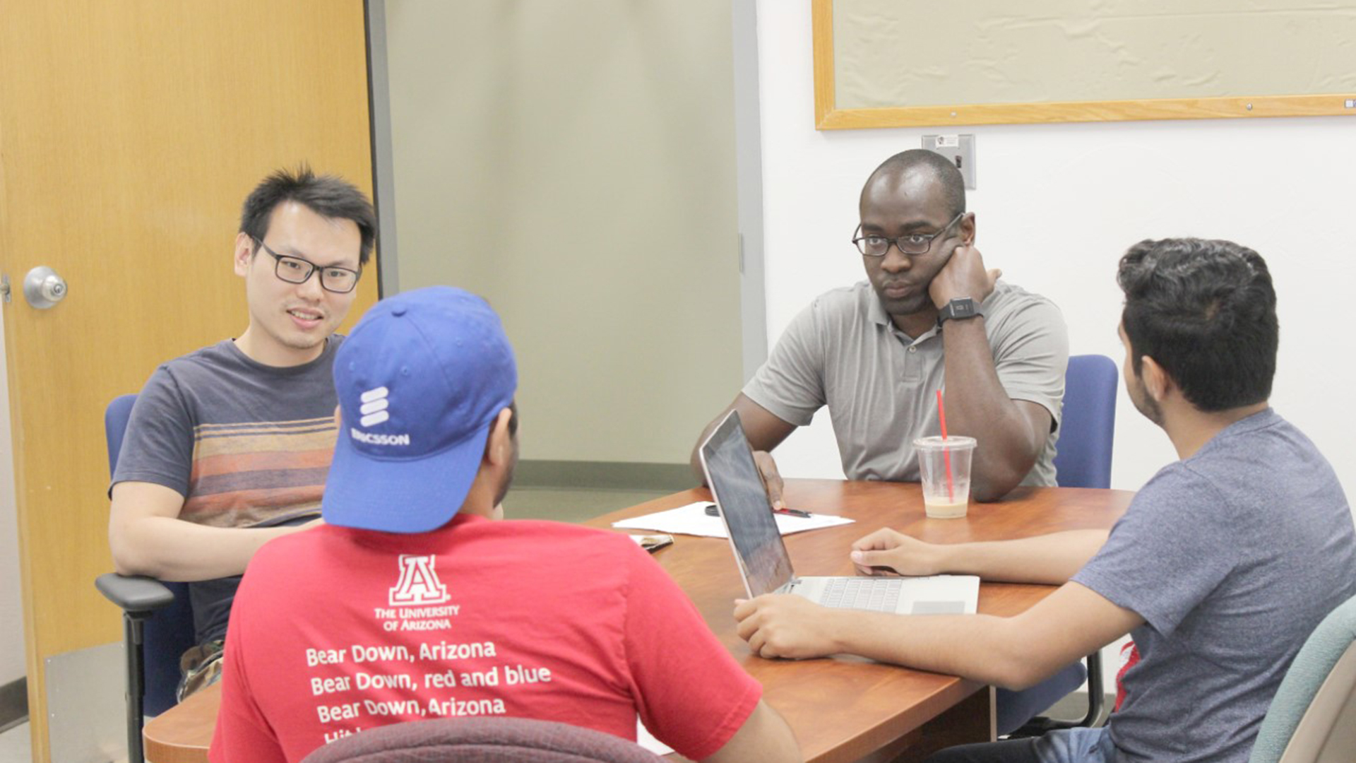 Tosi Adegbija, center, listens as UA students discuss computer engineering proposals.