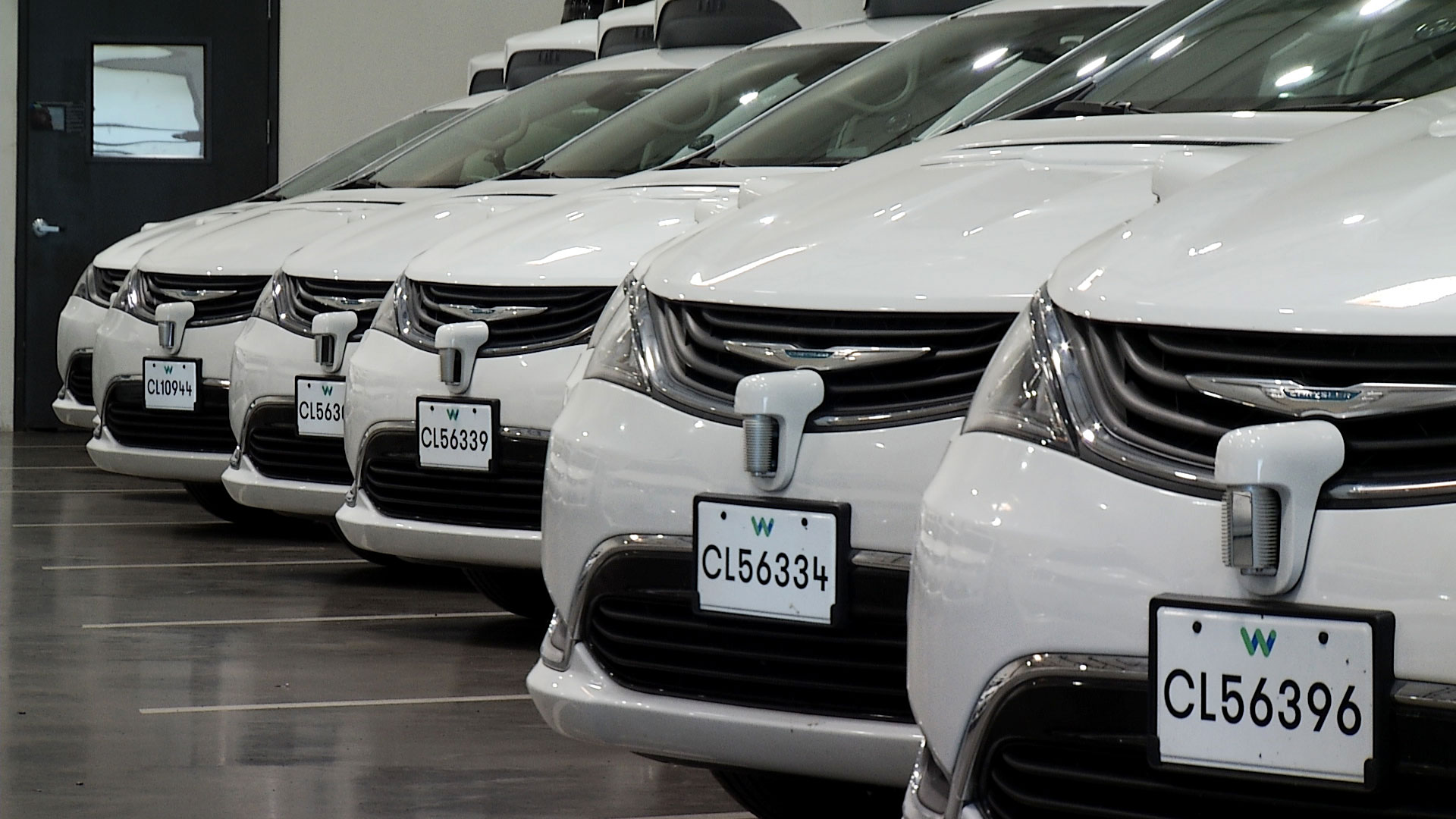 A row of vehicles outfitted with Waymo's self-driving technology sit parked in the company's depot in Chandler, Arizona.