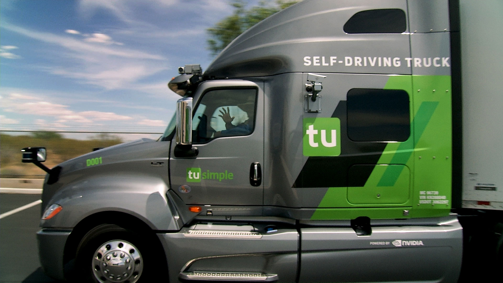 A TuSimple test driver waves from inside a self-driving semi as it leaves the company's warehouse in Tucson.