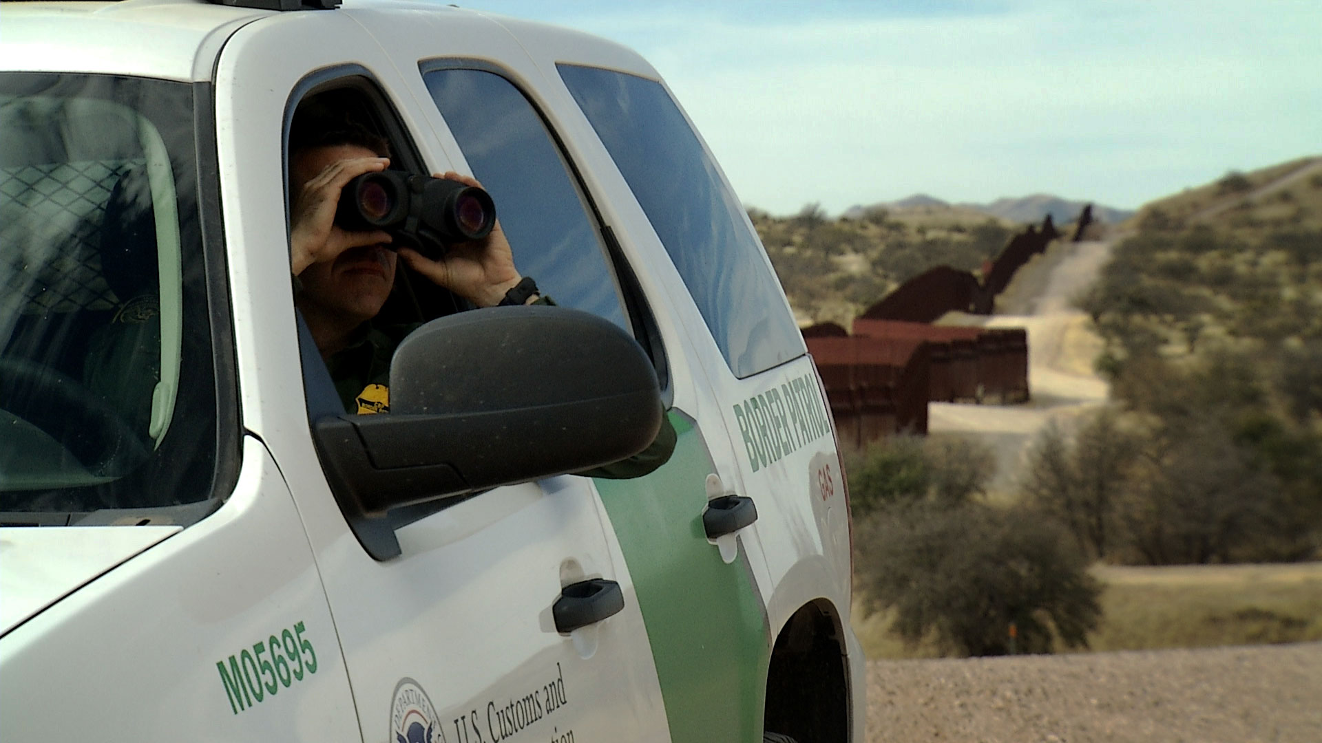 File image of a Border Patrol agent using binoculars to surveil an area just north of Arizona's border with Mexico.