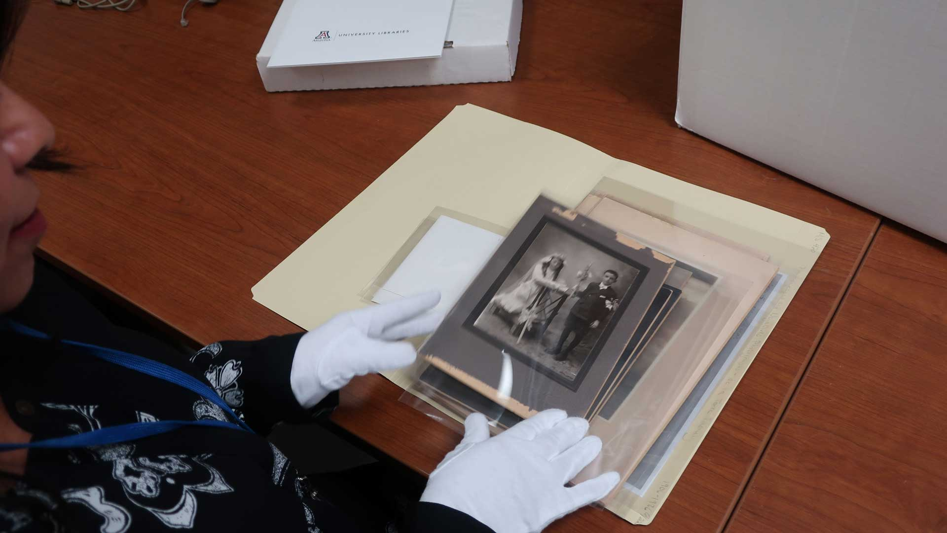Verónica Reyes-Escudero examines photos from the de la Torre family collection at UA Special Collections.