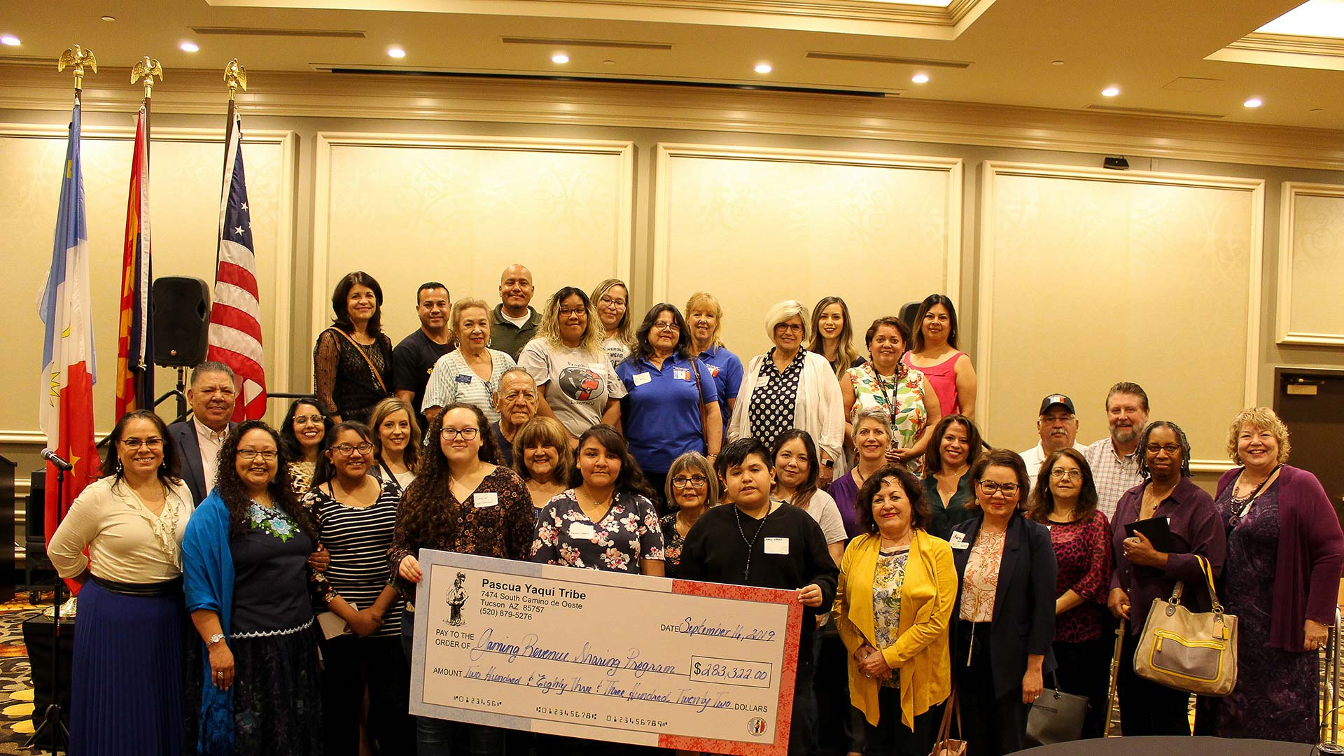 Tribal officials and representatives from the 14 organizations that received a grant through the Pascua Yaqui Tribe's gaming contributions pose September 16, 2019, with a check for the total amount donated to the organizations.