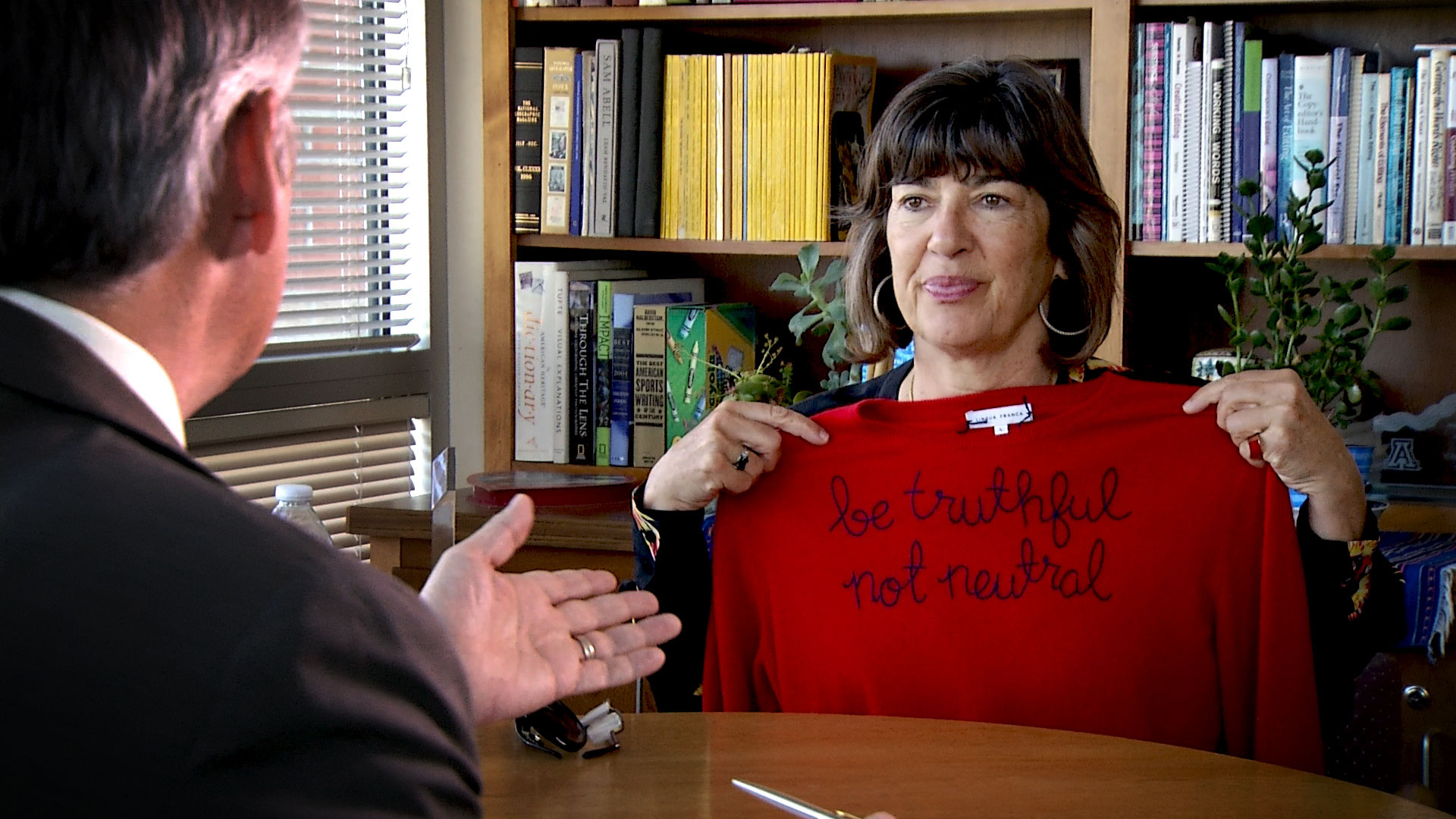 "Journalist Christiane Amanpour shows AZPM reporter Christopher Conover a sweater embroidered with her motto, ""be truthful, not neutral,"" during an interview for Arizona 360 on September 20, 2019."