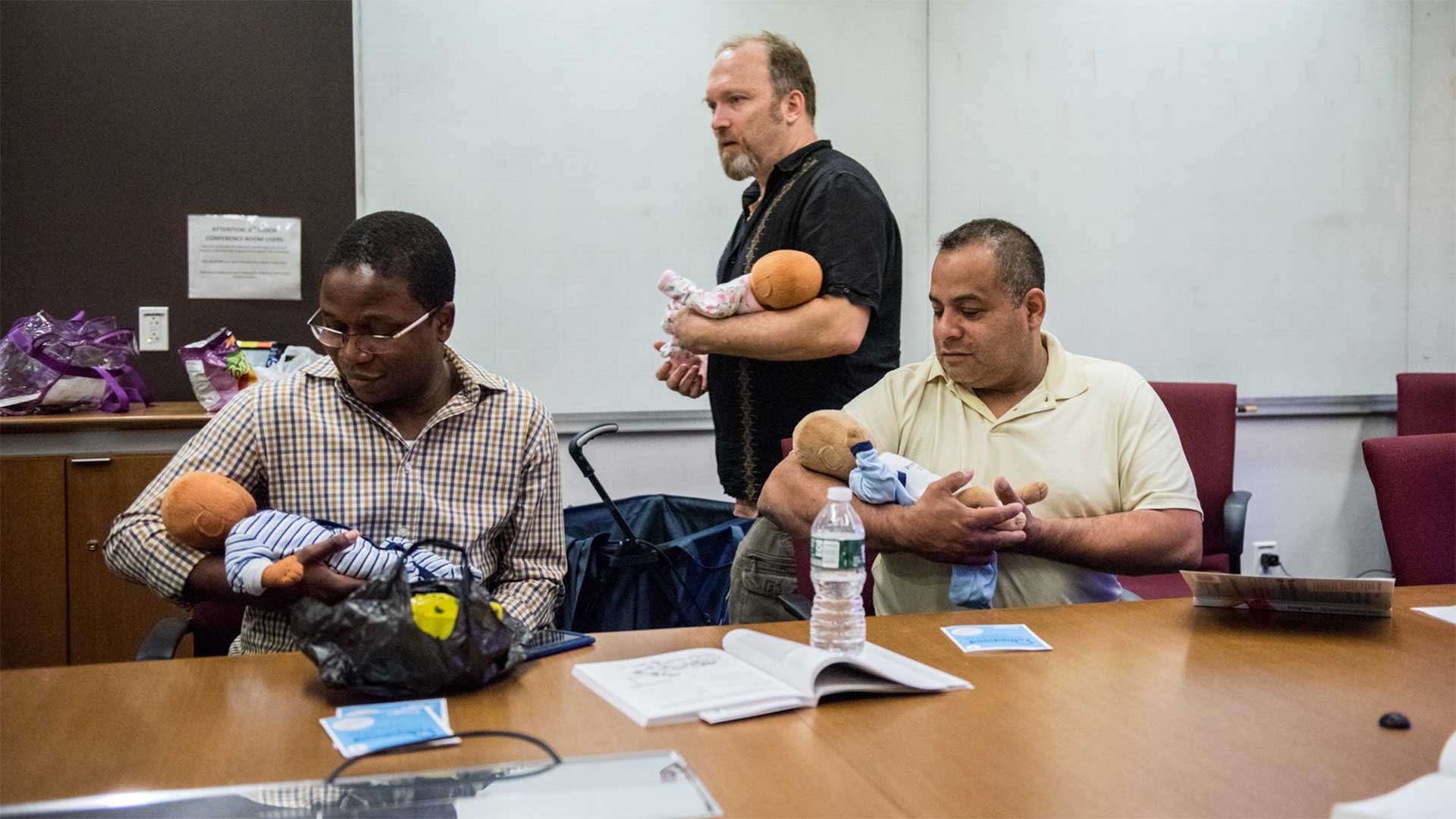 "Joe Bay (center), coach of a New York City ""Bootcamp for New Dads,"" instructs Adewale Oshodi (left) and George Pasco in how to cradle an infant for best soothing."