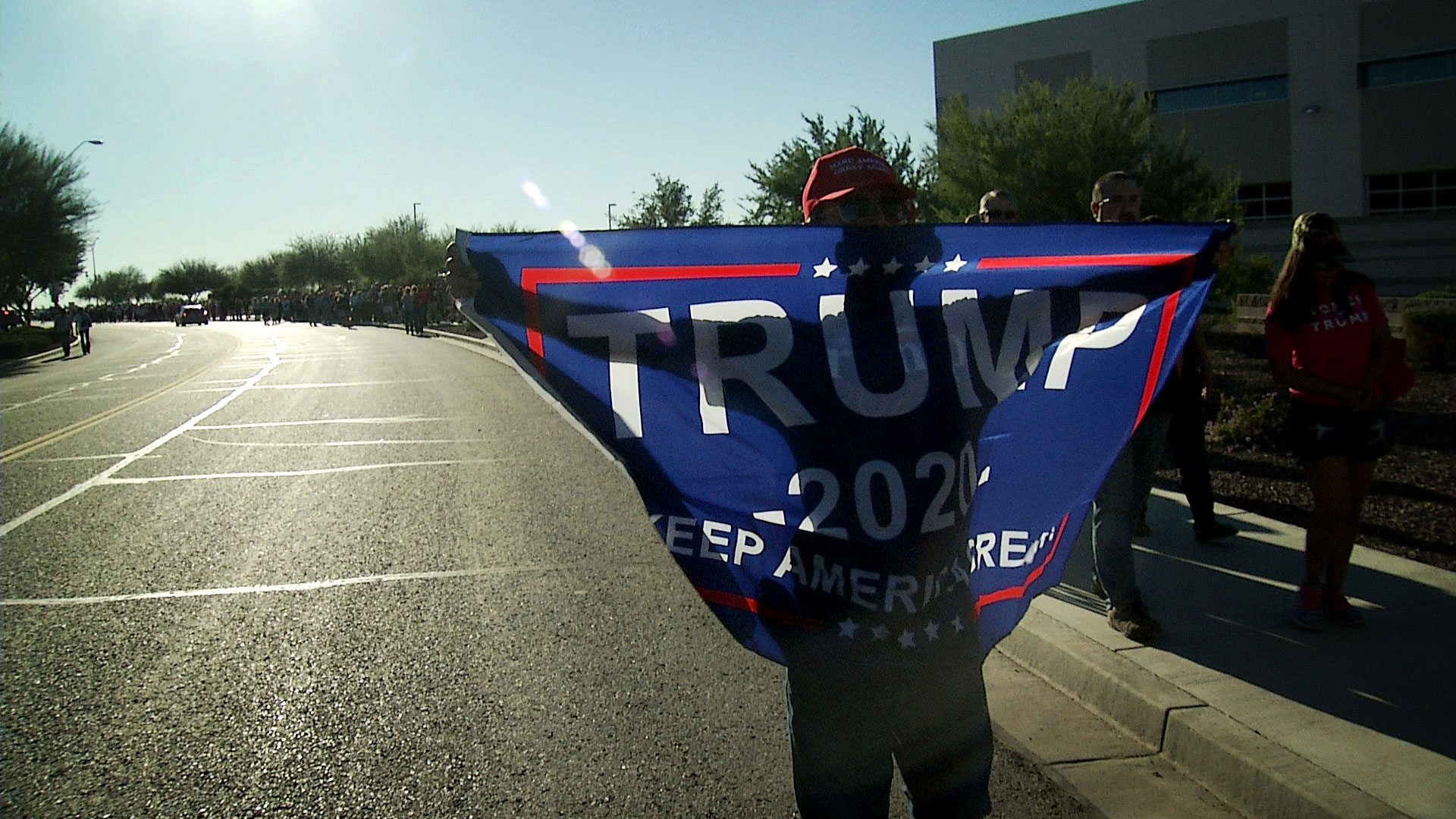 A President Trump supporter holds up a Trump 2020 campaign flag outside of the venue for the president's rally at the Phoenix-Mesa Gateway Airport on Oct. 19, 2018.
