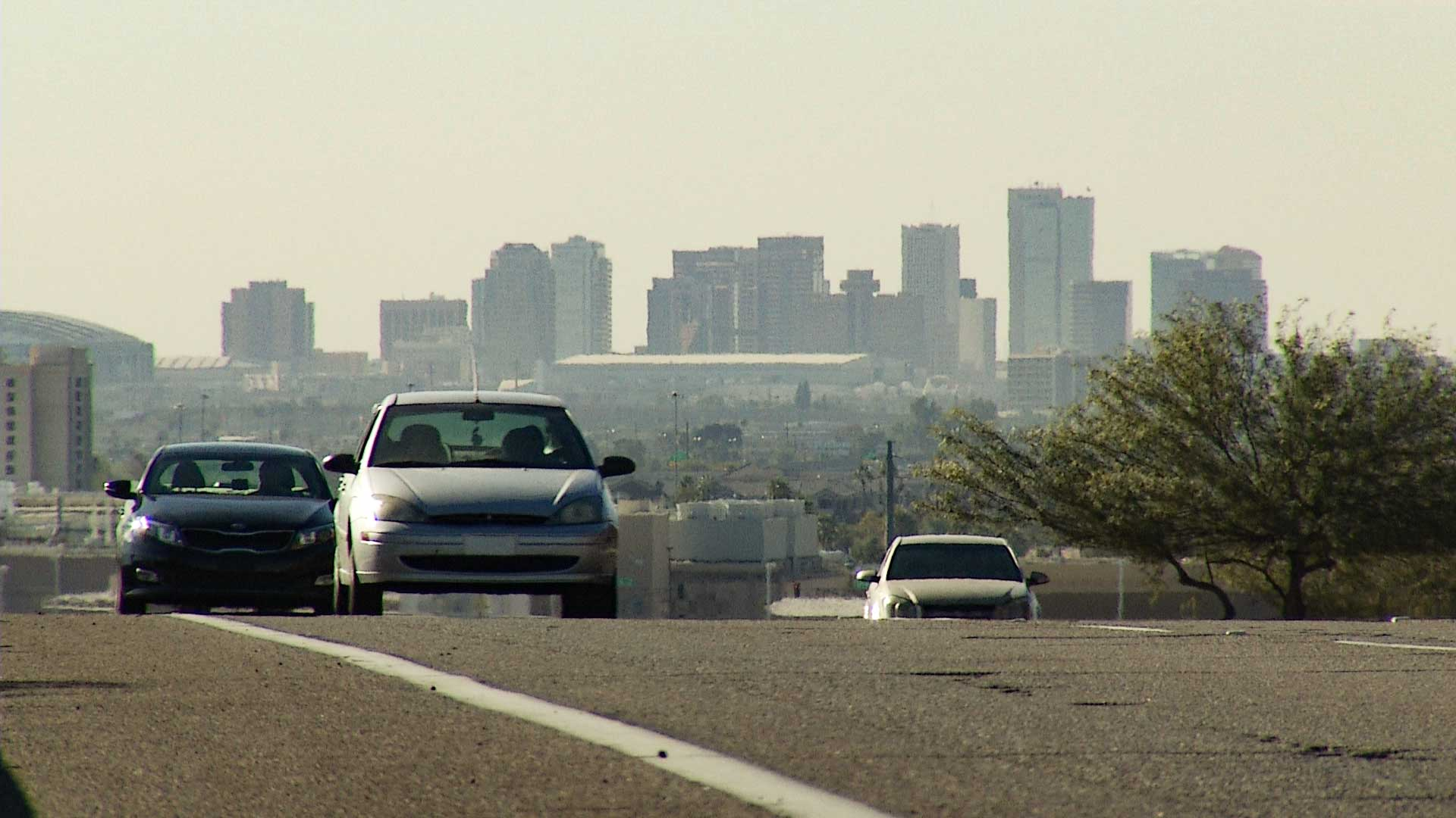 Cars driving with downtown Phoenix in the background
