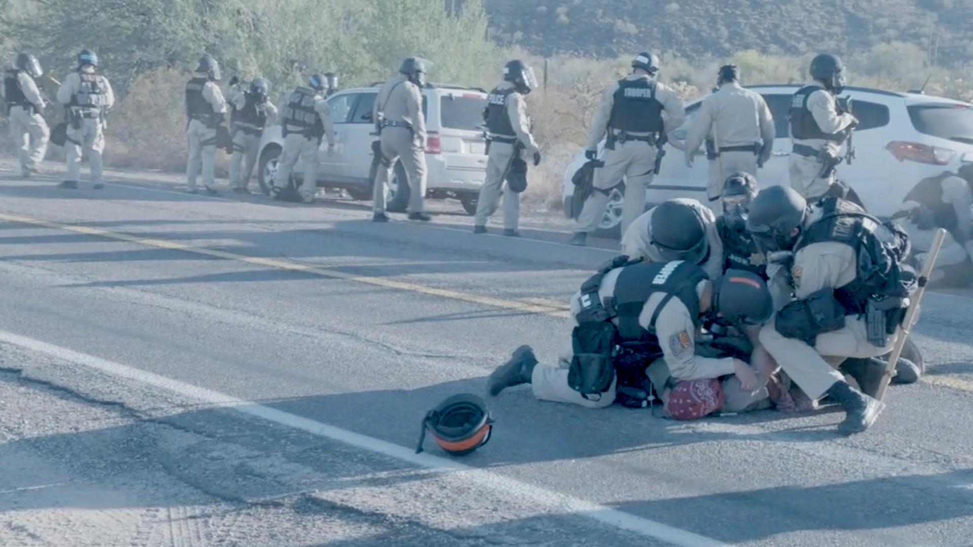 Arizona Department of Safety officers surround and handcuff an Indigenous demonstrator during an O'odham-led blockade at a Border Patrol checkpoint on Highway 85 on October 12, 2020.
