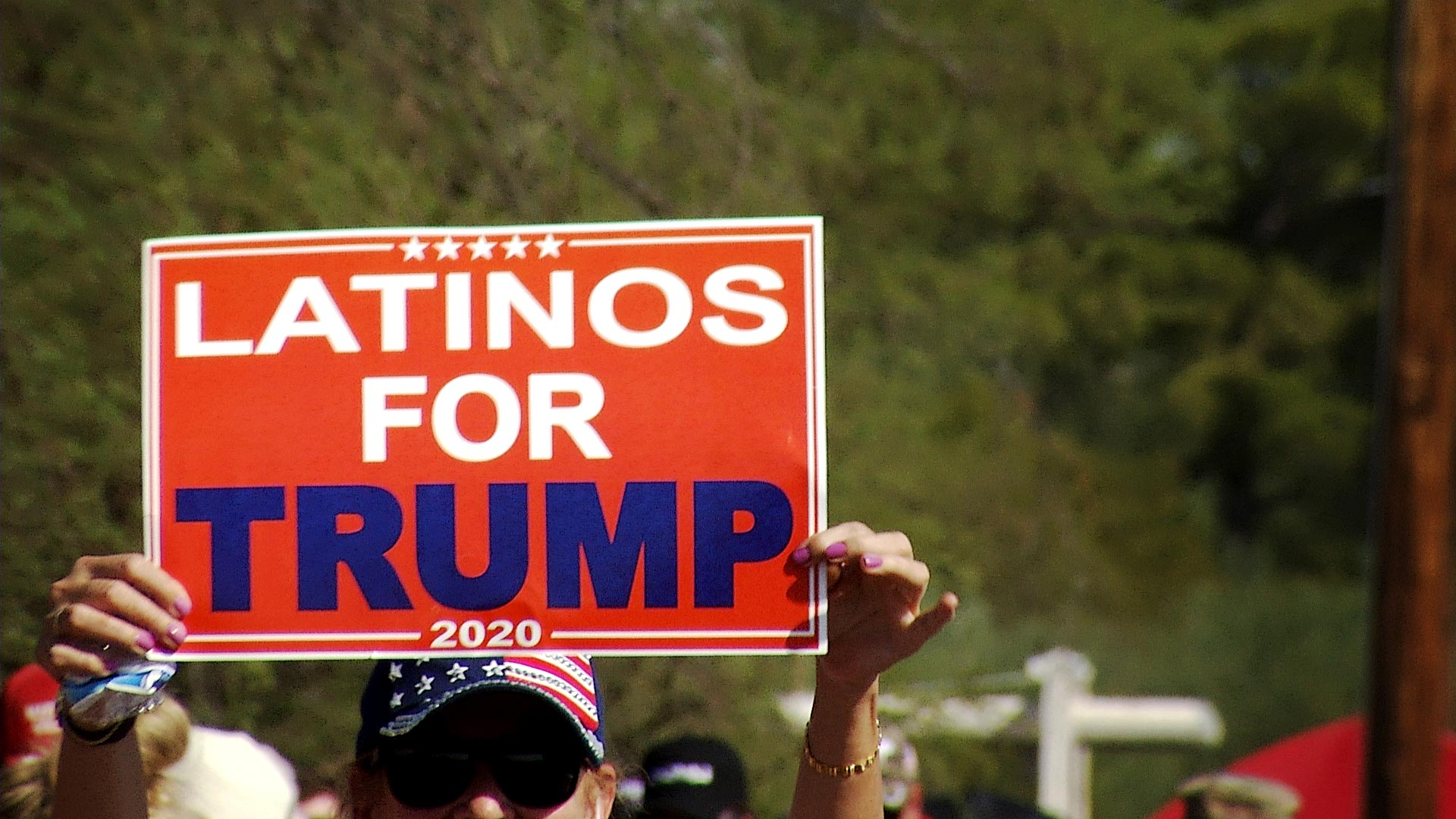 "A woman holds up a ""Latinos for Trump"" sign outside of Tucson International Airport where President Trump held a campaign rally on Oct. 19, 2020."