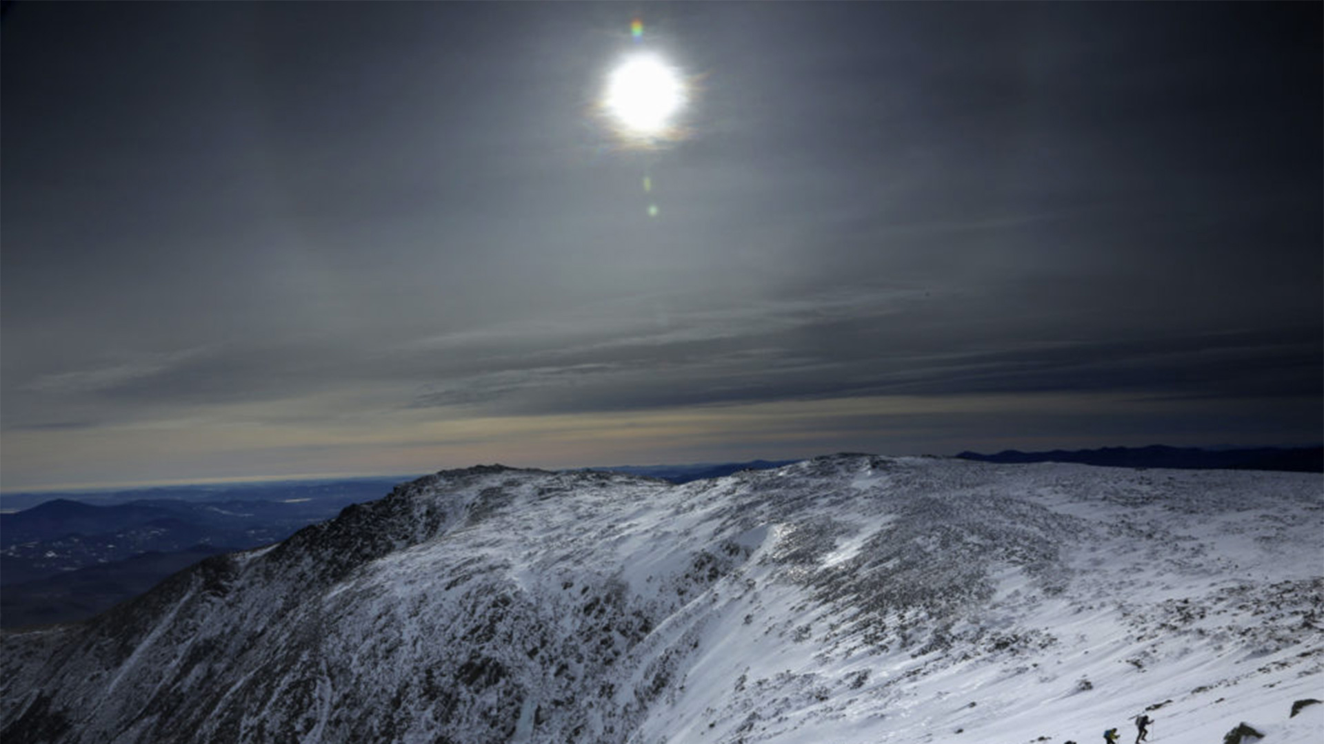Under a midday winter solstice sun, a trio of climbers make their way up a slope on Mount Washington, Saturday, Dec. 21, 2019, in New Hampshire.