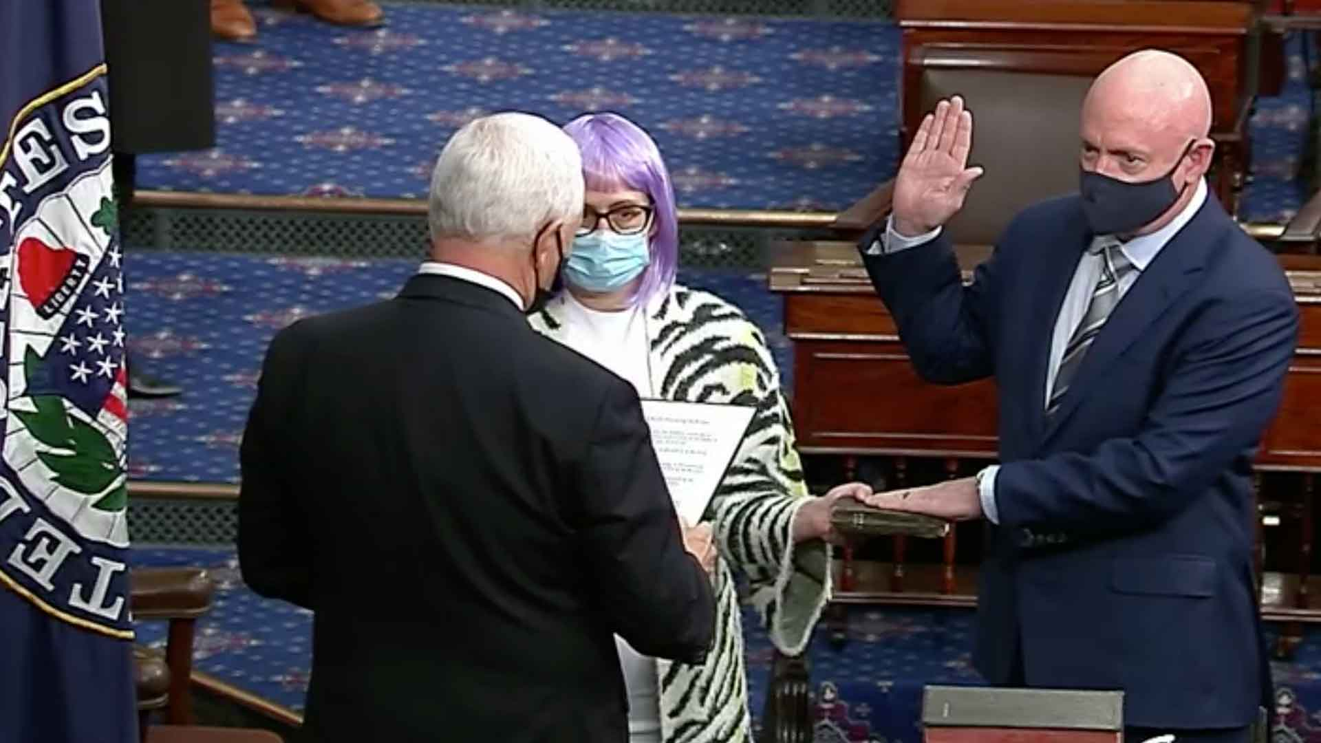 Sen. Mark Kelly is sworn into office by Vice President Mike Pence on Dec. 2, 2020.  Kelly was joined by Sen. Kyrsten Sinema.