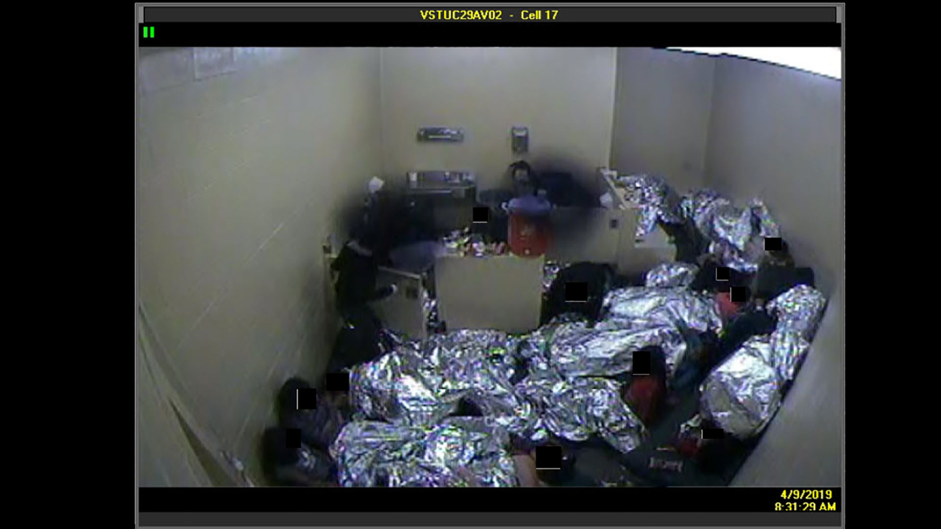 An image from a video camera in a Customs and Border Protection immigrant processing facility in the Tucson-area shows the overcrowding, with detainees forced to wrap themselves in Mylar blankets and sleep on the floor or sitting against a wall.