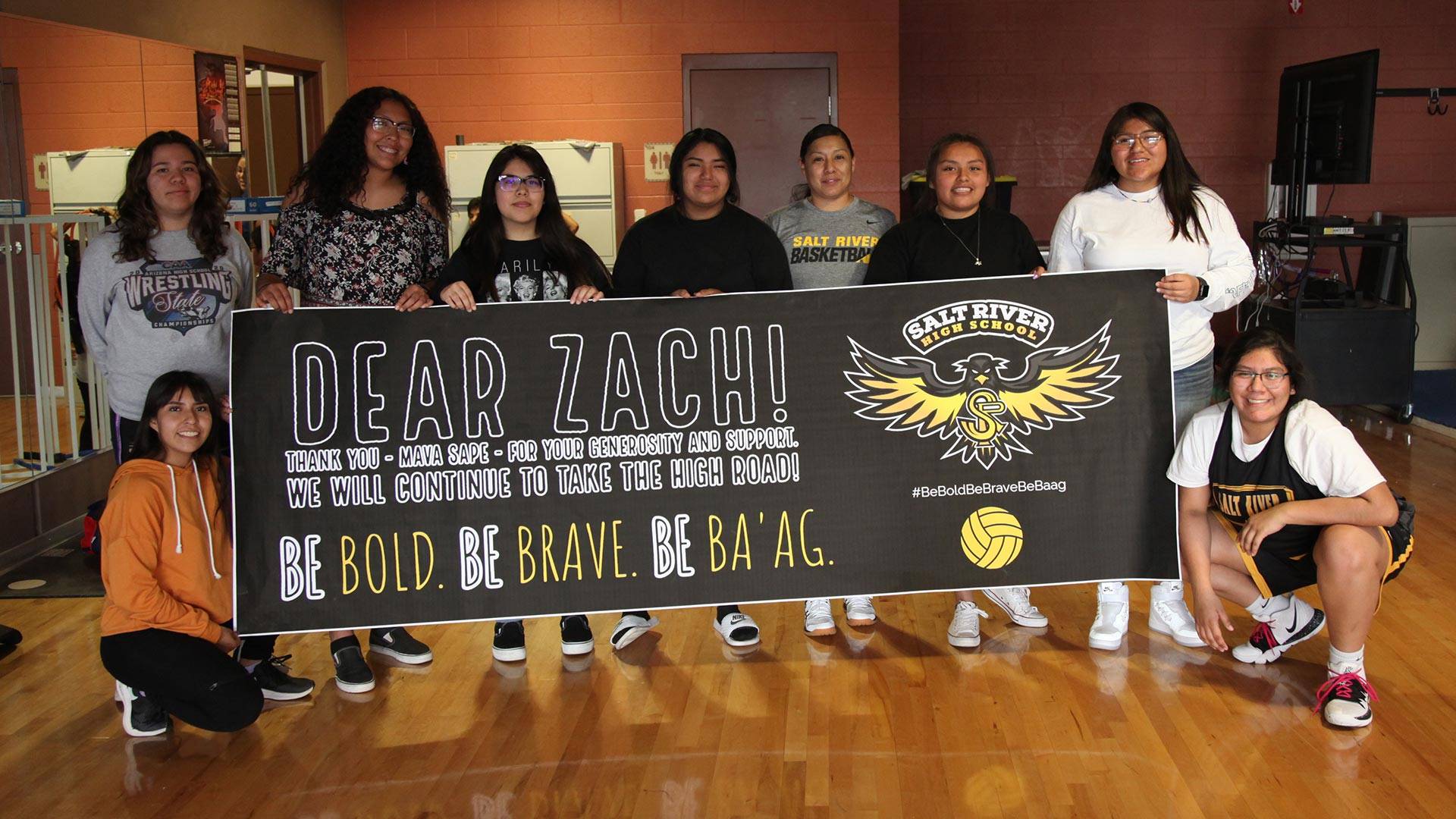 "Salt River High School volleyball girls display a sign thanking Zach Galifianakis for donating to their team. They say his donation is a response to their game on Oct. 22, 2020, in which they say spectators called them ""savages"" and made offensive gestures."