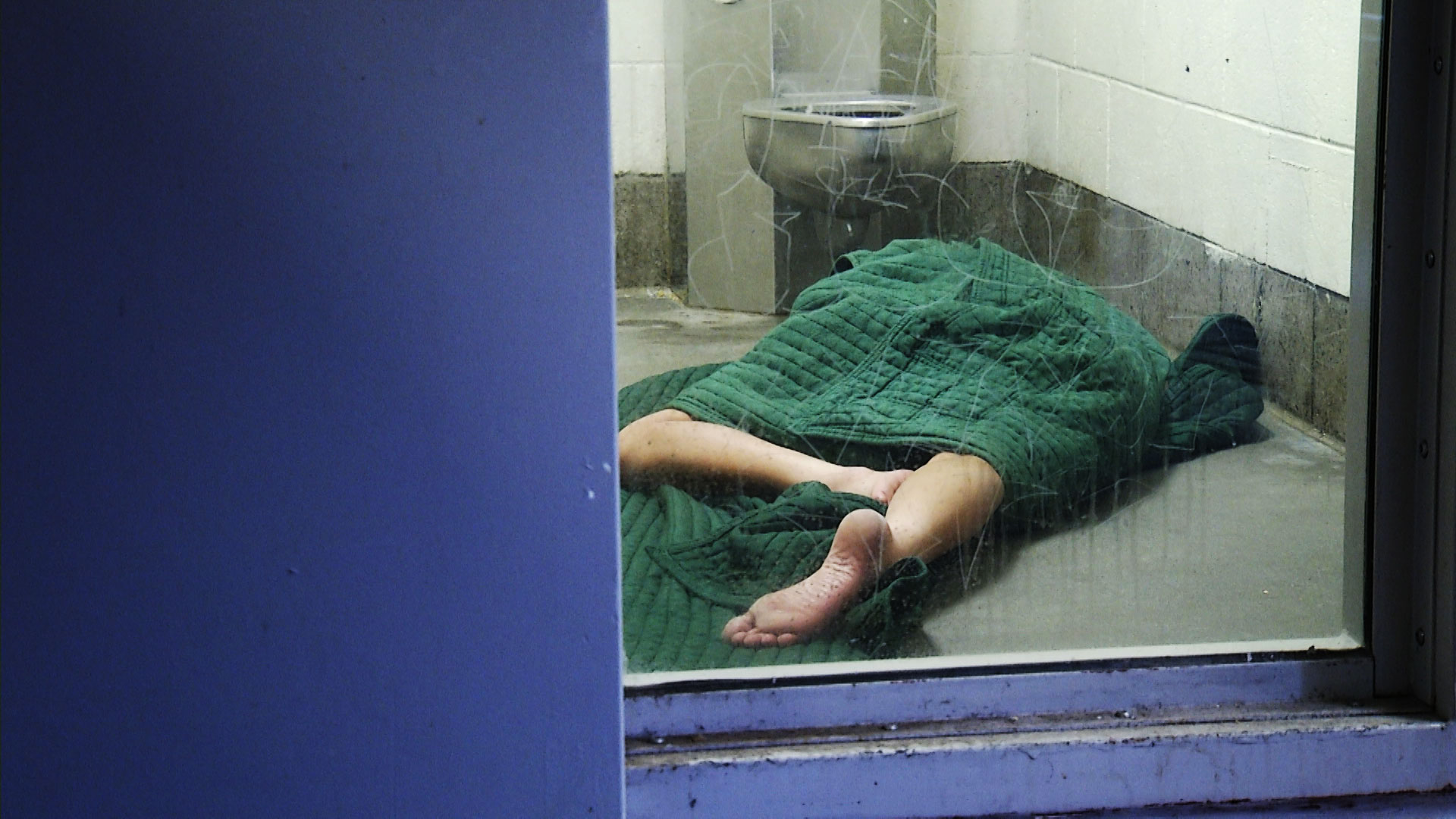 An inmate lies on the floor under a blanket in his cell at the Pima County Adult Detention Complex.