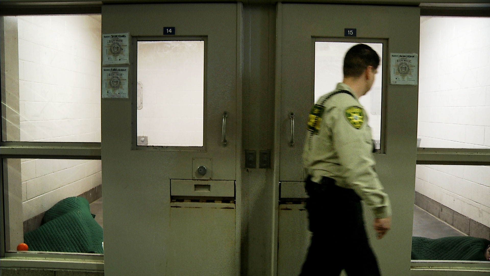 A Pima County correctional officer glances inside a cell at the county jail.