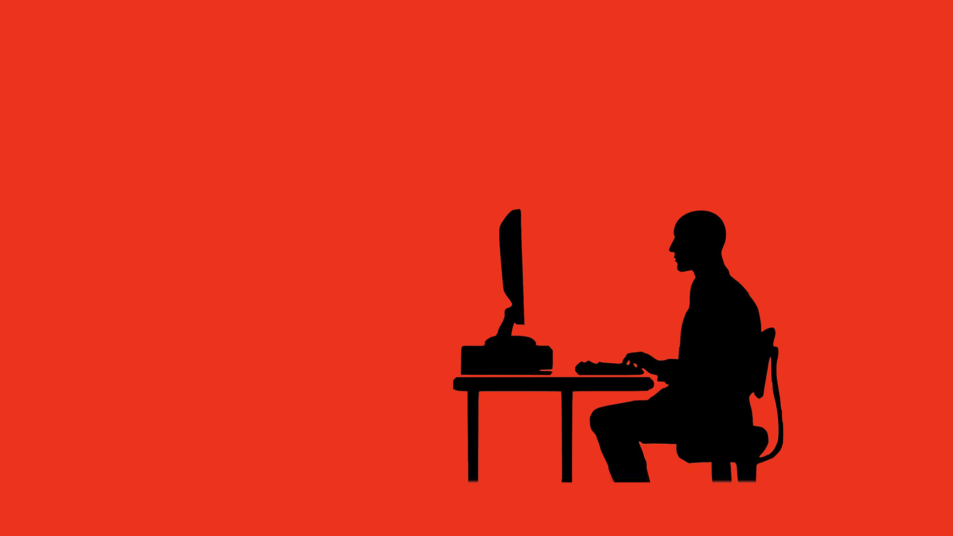 Silhouette of man sitting at computer with red background.