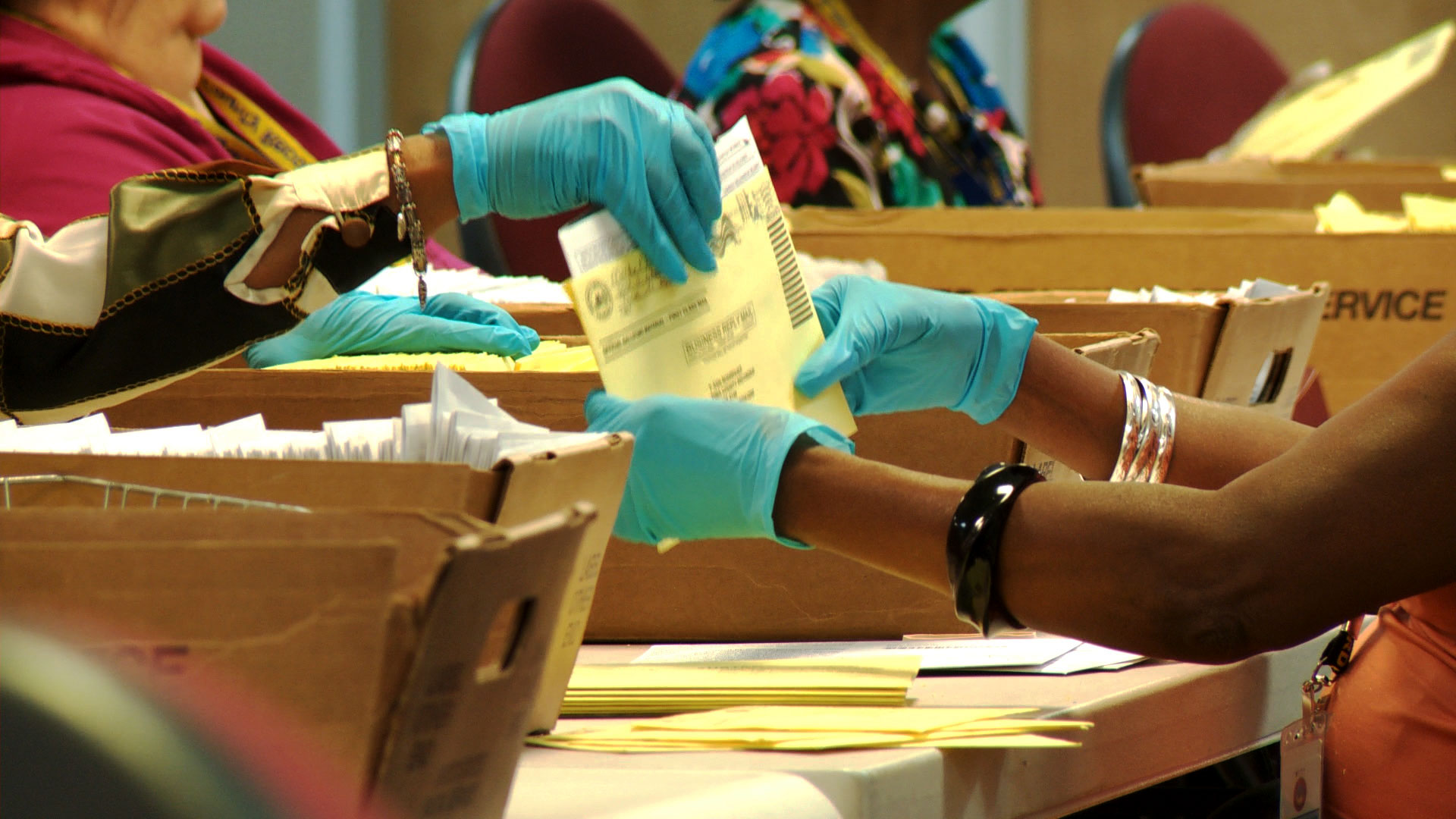 Election workers process mail ballots at the Pima County Elections Department.