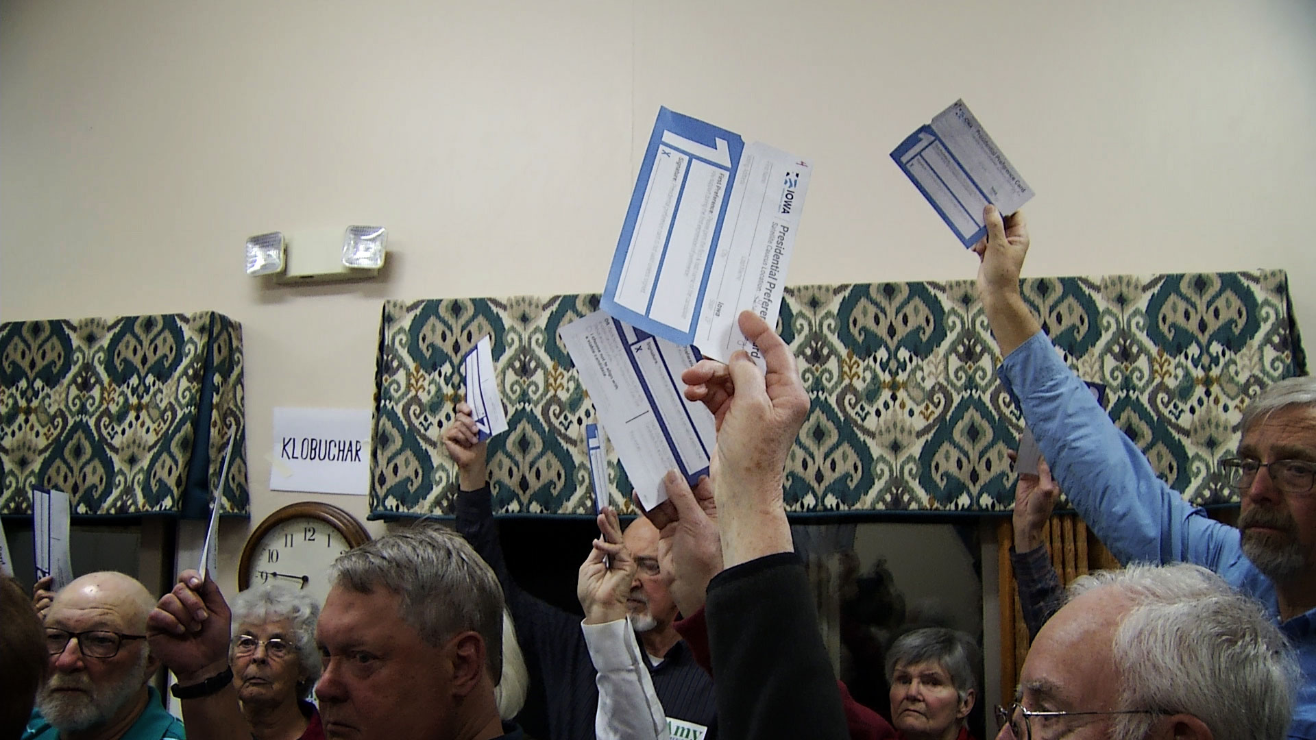 Registered voters from Iowa raise their presidential preference cards in the first alignment of the Democratic Iowa caucus at a satellite location in Green Valley on Feb. 3, 2020.