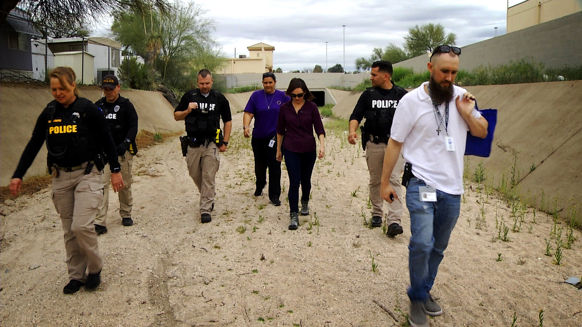 Arizona 360 host Lorraine Rivera (center) walks through a wash with members of the Tucson Police Department's Substance Use Resource Team on March 10, 2020. In an area common for drug use, Rivera saw how officers implement the department's Deflection Program that allows them to offer people treatment for drug-related crimes instead of arrest.