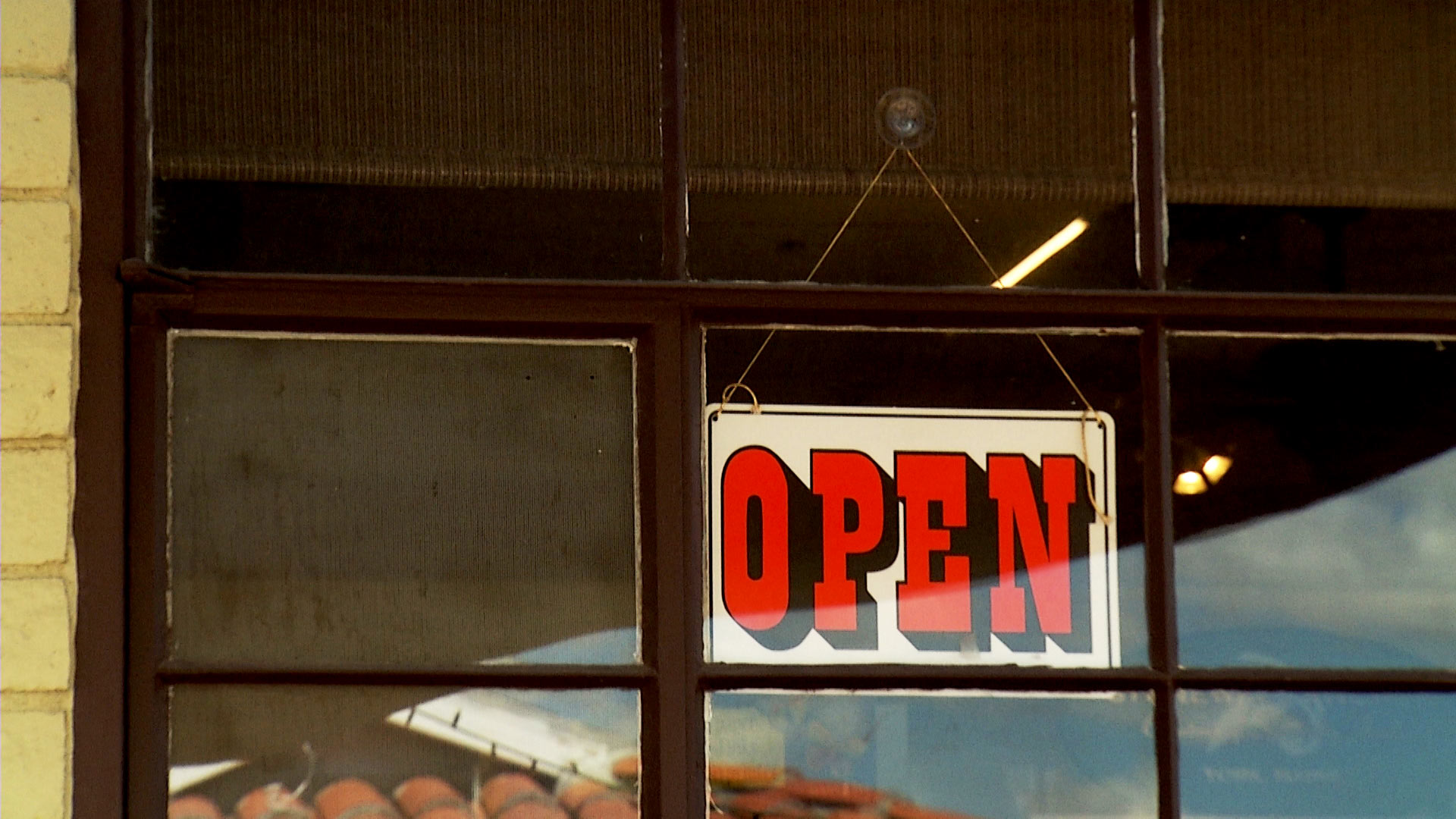 An open sign hangs in the window of a business in Patagonia.