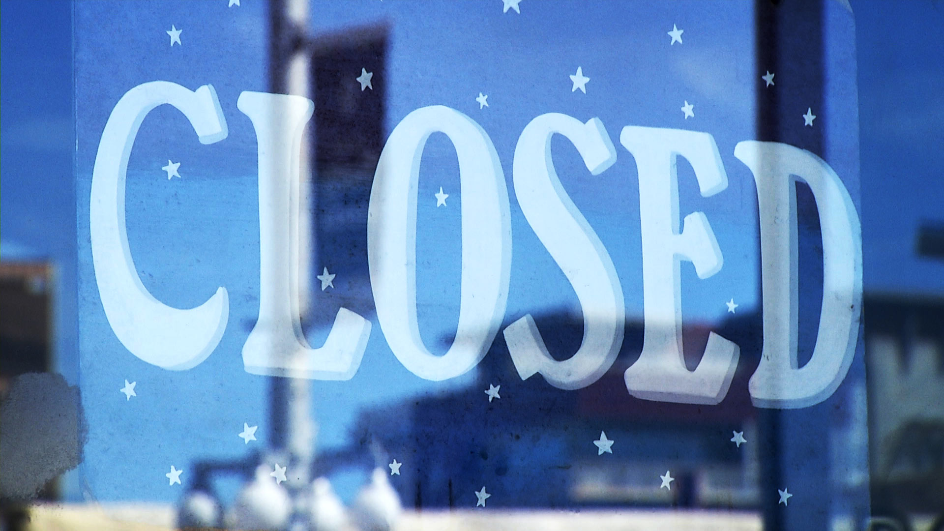A closed sign hangs in the storefront of a business on 4th Avenue in Tucson.