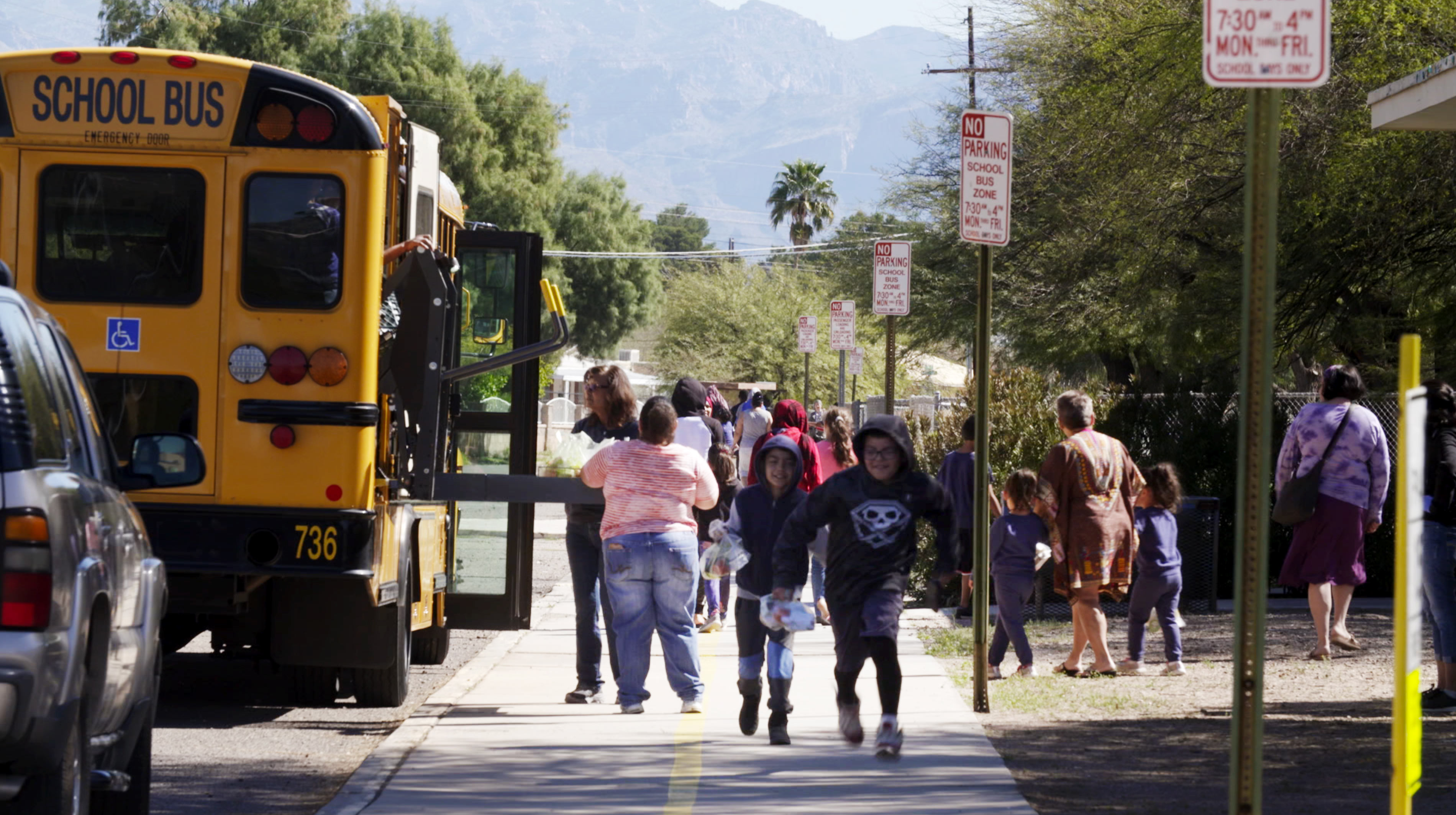 Students and families receive packaged meals from Tucson Unified School District workers who are distributing meals along the district's bus routes during closures associated with the COVID-19 pandemic.