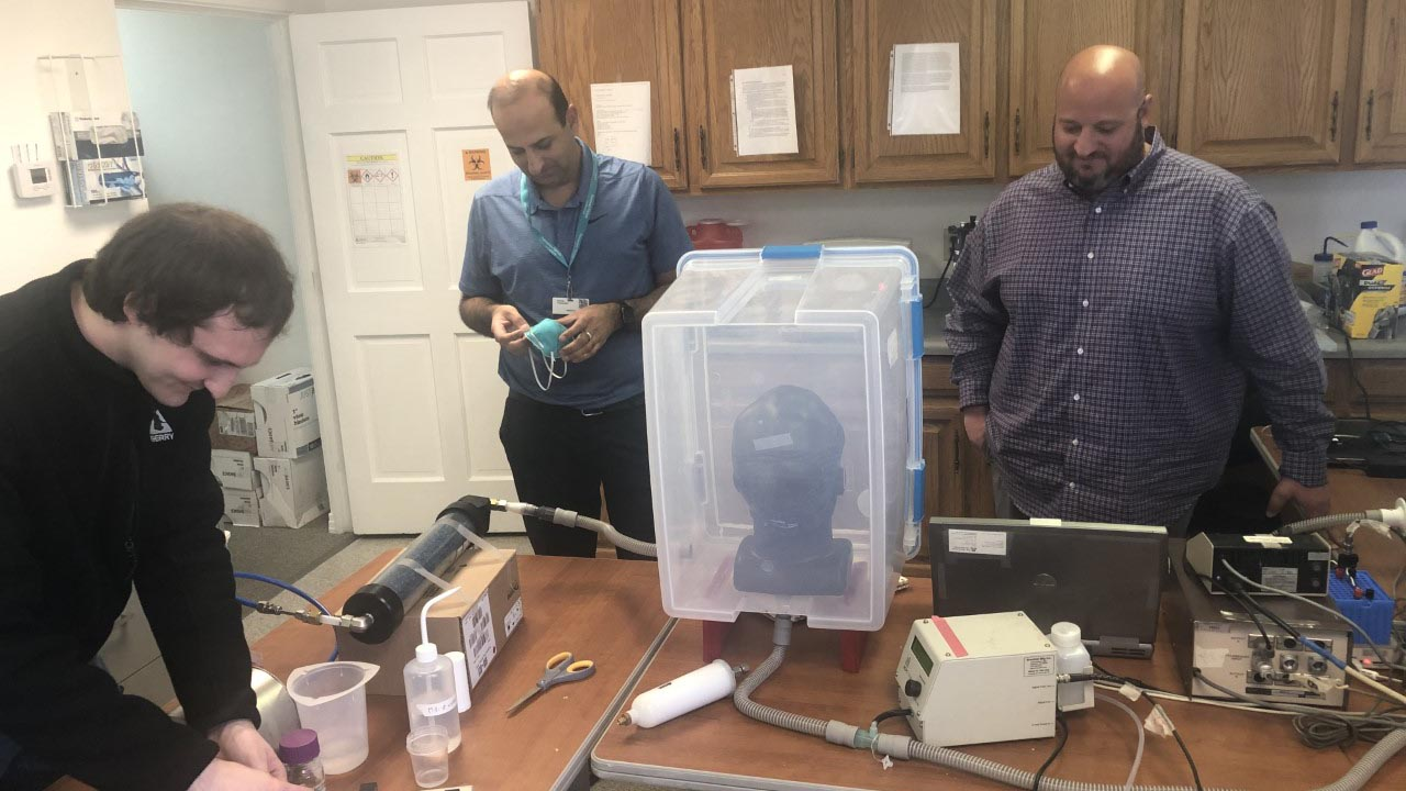 L-R researchers Connor Stahl, Sachin Chaudhary M. D., and Christopher Morton prepare to test 3D printed respirator mask at the University of Arizona