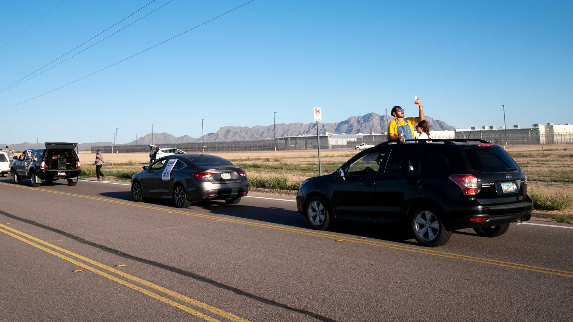 A line of cars drives past the La Palma Detention Center in Eloy, Arizona. Demonstrators honked horns and hung banners from their windows calling for thge release of detainees in the wake of the coronavirus.