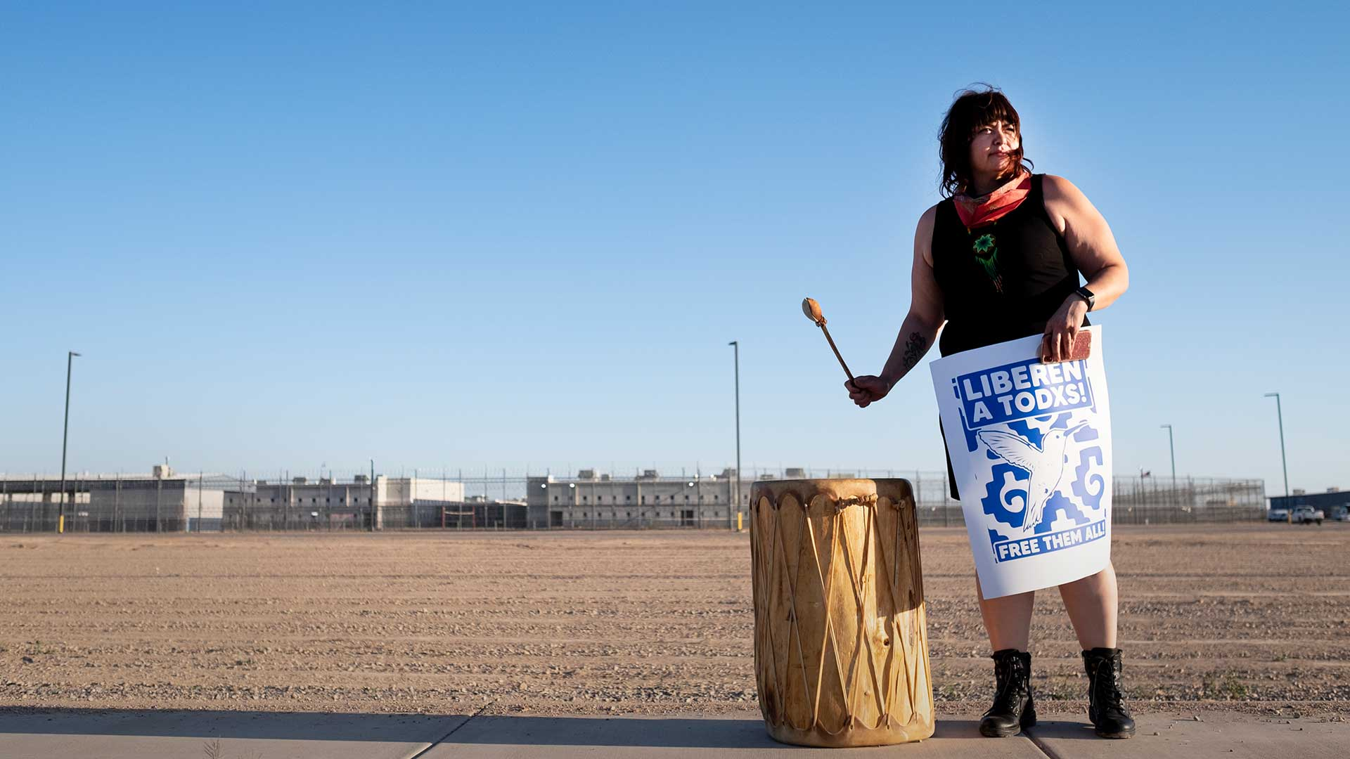 A protester bangs a drum on the sidewalk outside the La Palma Detention Center in Eloy, Arizona. Protesters in over 200 cars circled the facility on on April 10 calling for the release of detainees in the wake of the coronavirus pandemic.