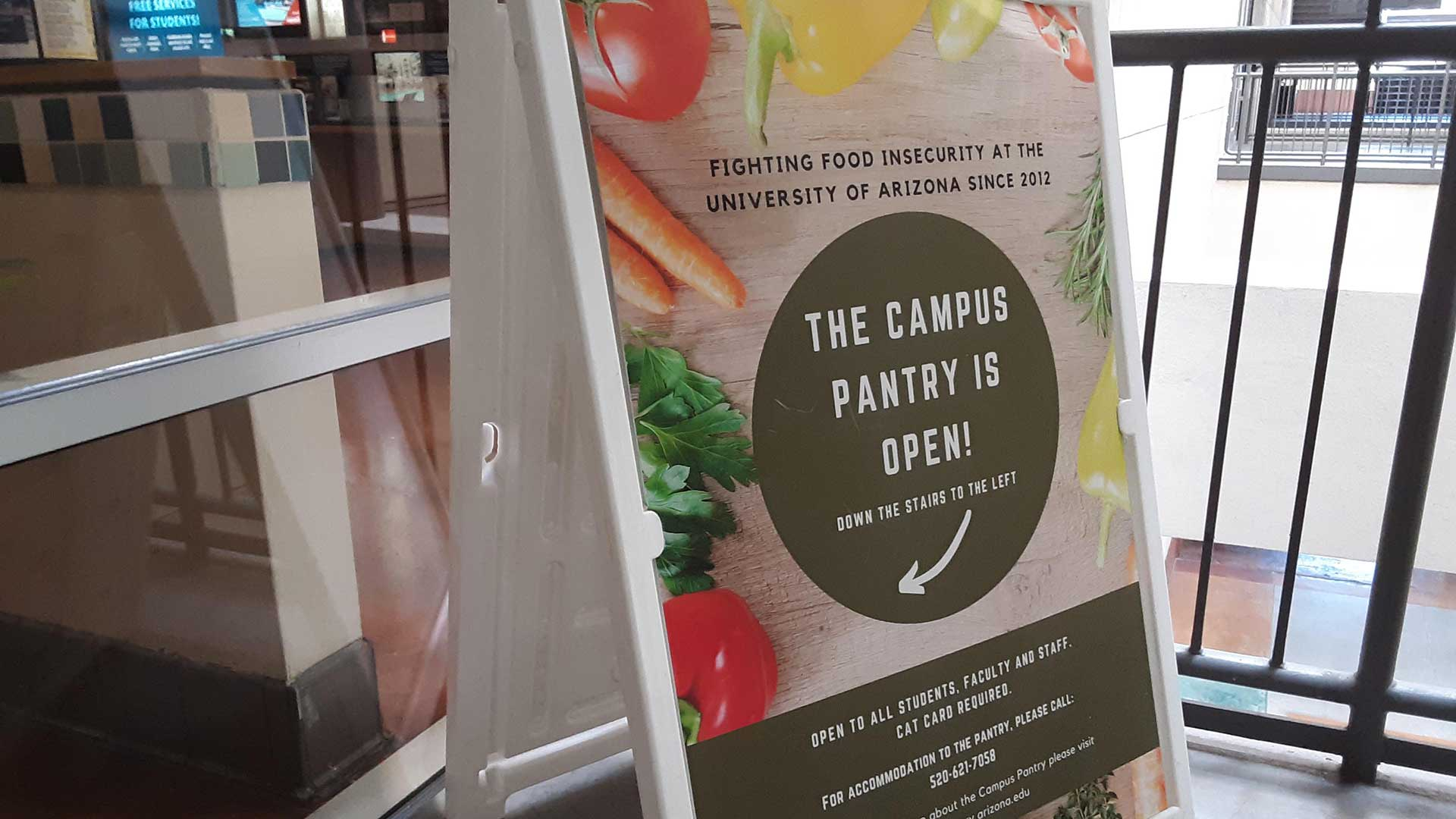 A sign points to the new UA Campus Pantry location at the Student Union Memorial Center
