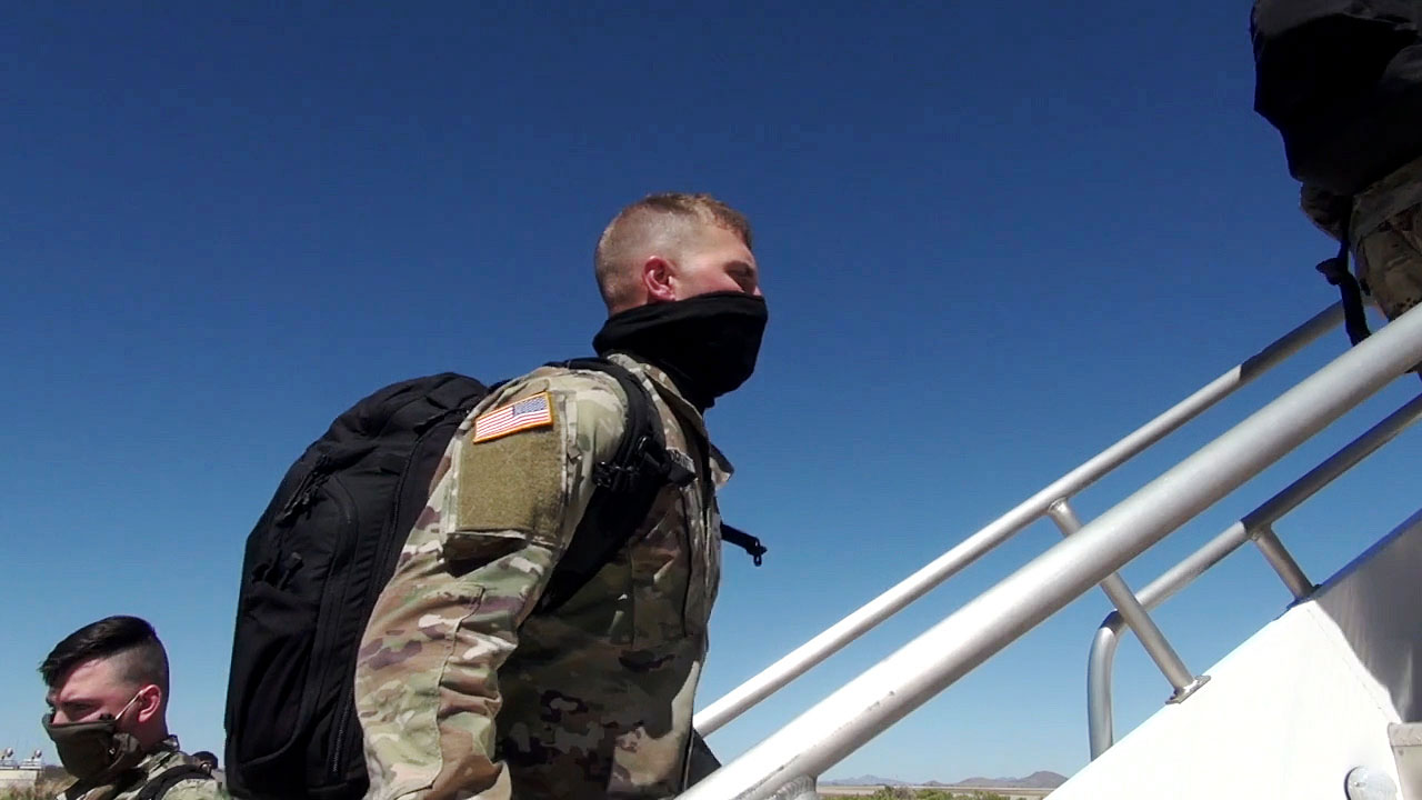 A soldier in a masks boards a plane at Fort Huachuca in Sierra Vista on the way to his next duty station, April 2020.